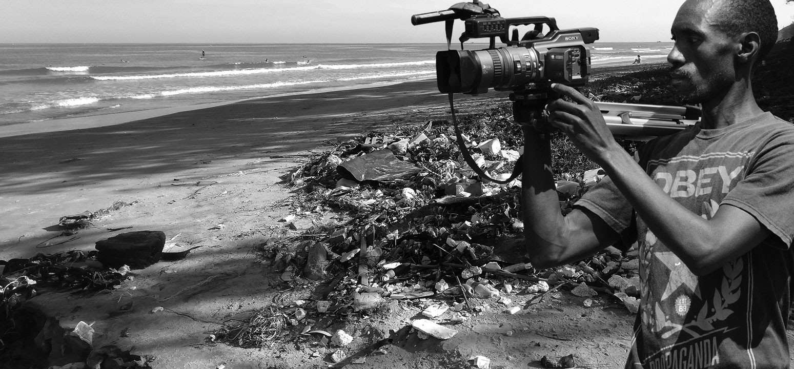 Video cameraman recording pollution on a beach