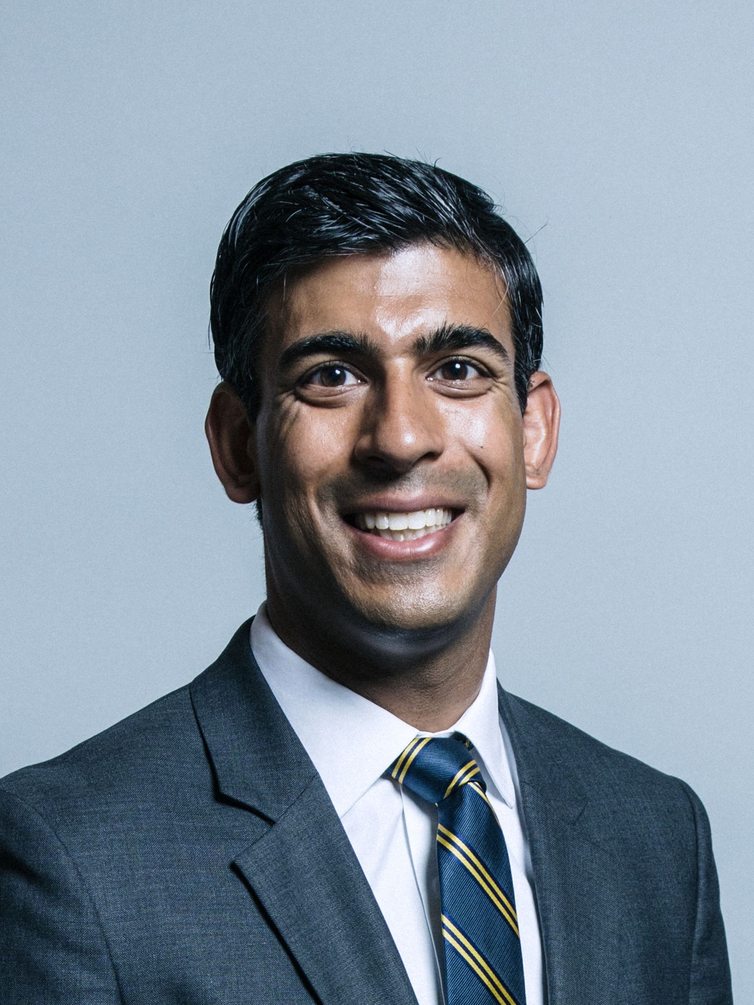 A photo of British Chancellor of the Exchequer Rishi Sunak MP staring at the camera, smiling and wearing a business suit