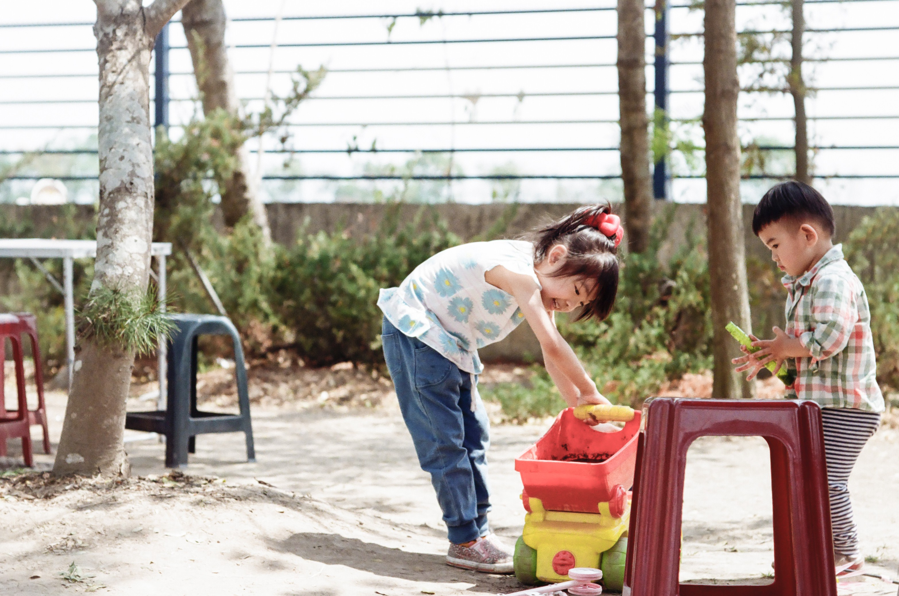 Two small children playing with a truck in a sandpit