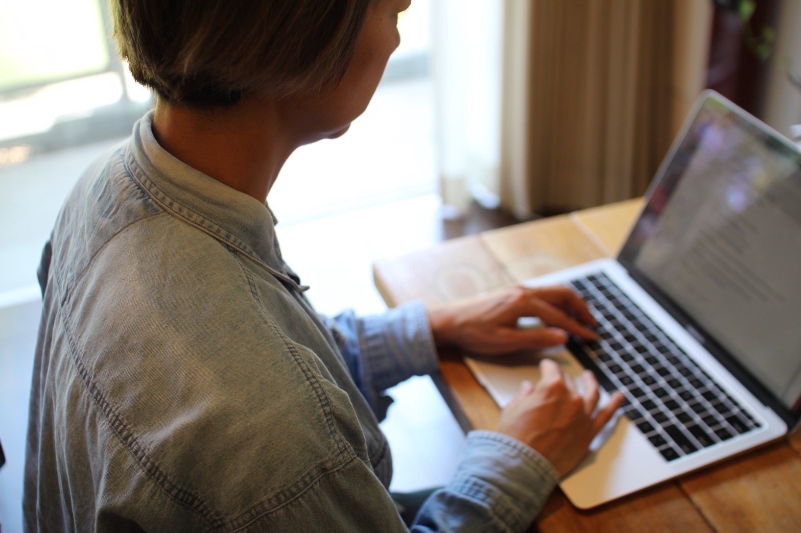 A woman works on her laptop computer at home during COVID-19.