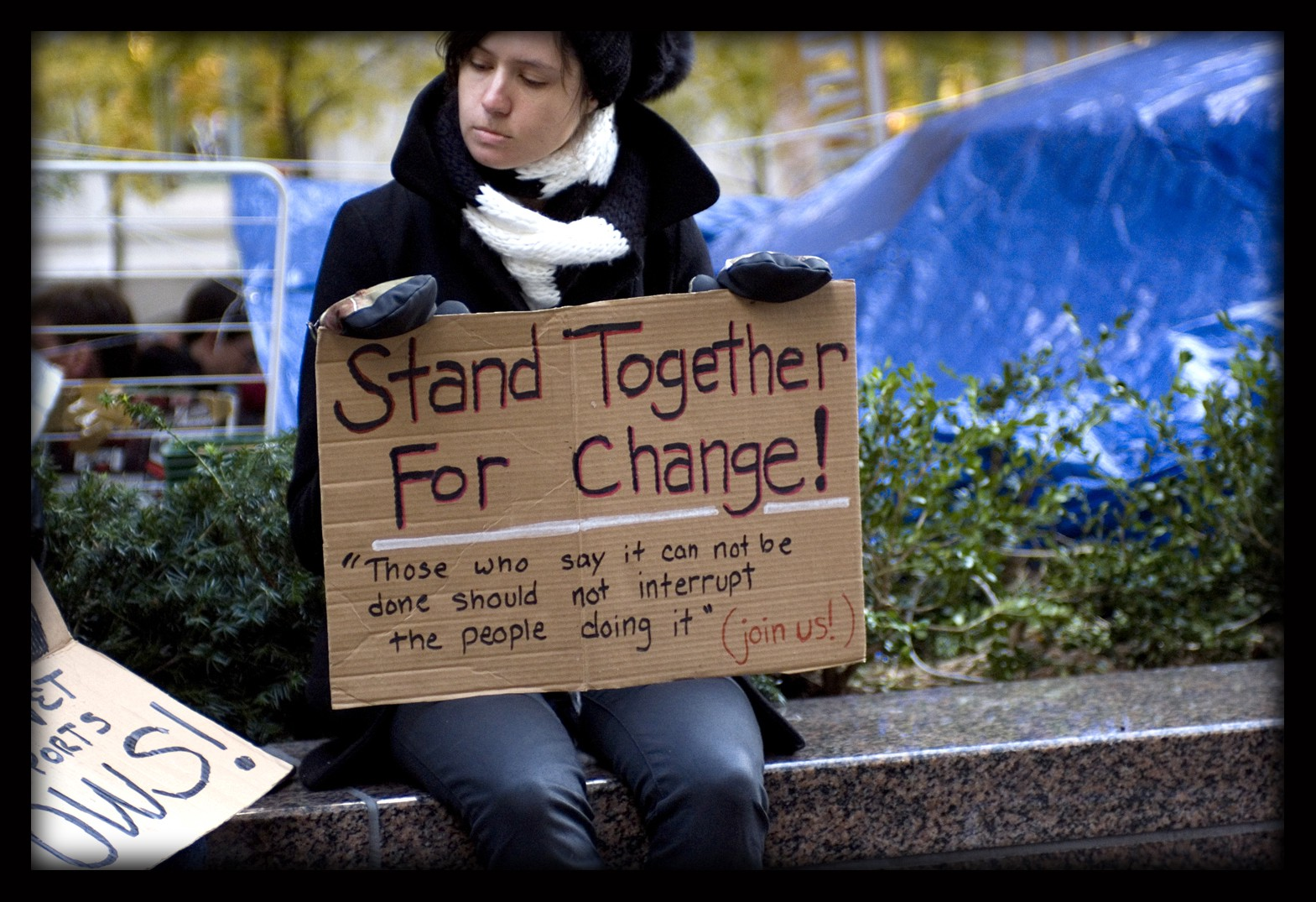 """A woman in jeans and a black coat and black and white scarf sitting on a concrete bench at Occupy Wall Street, with a blue tarp in the background. She is holding a sign that reads """"Stand together for change! Those say it can not be done should not interrupt the people doing it. Join us!"""""""