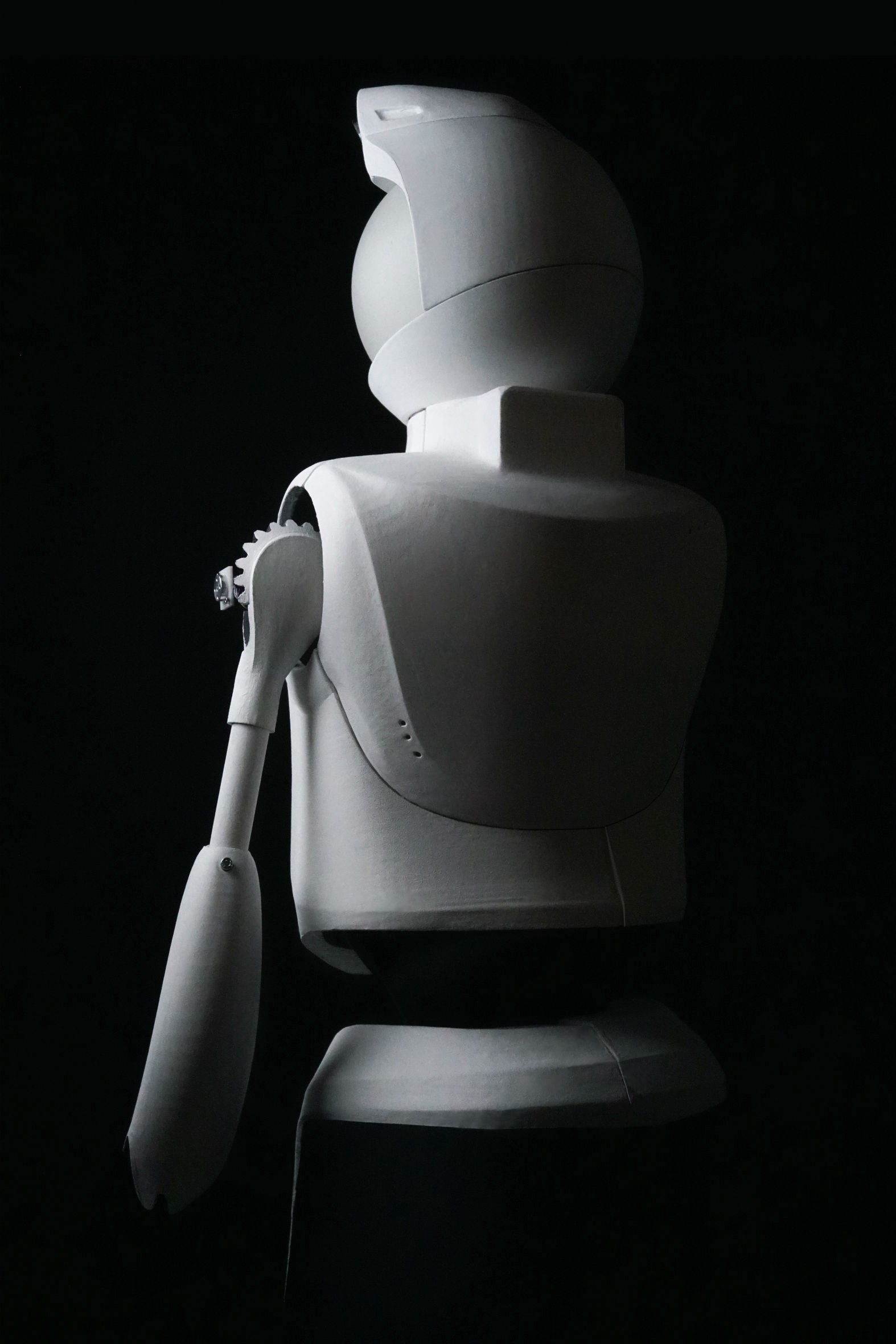Dramatic black and white photo of Quori robot taken from behind. Shadow falls on robot's back and looks ominous.