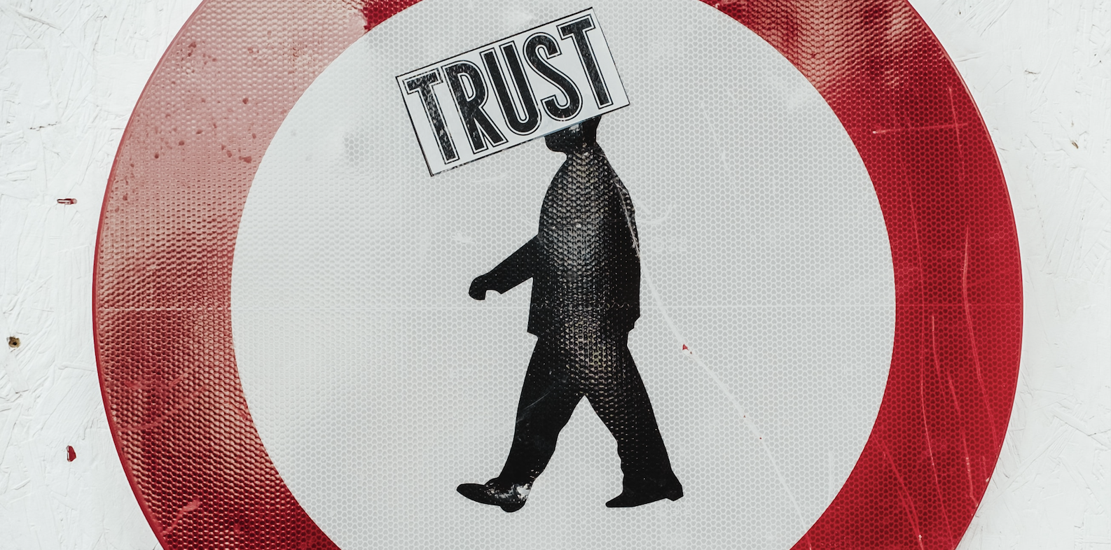 A pedestrian walking sign with a trust sticker on it