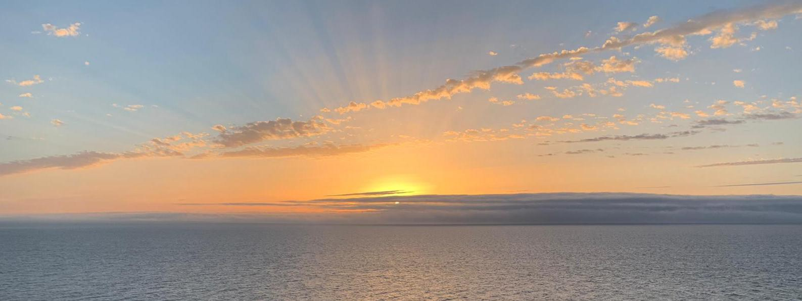 Sunrise on the Irish Sea showing the rays of the sun reflecting on the water.