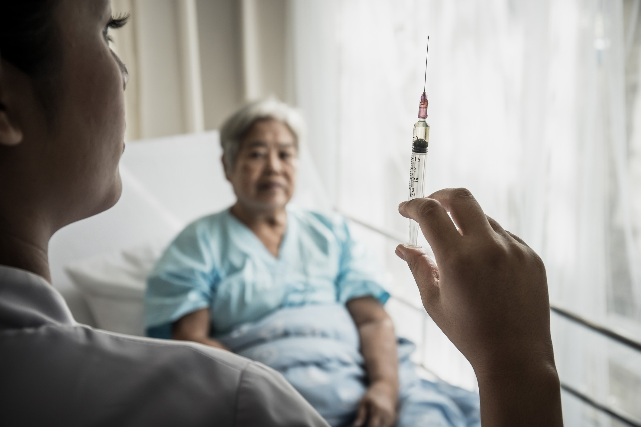 A photo of a nurse holding up a syringe with an elderly woman sitting in a hospital bed in the background.