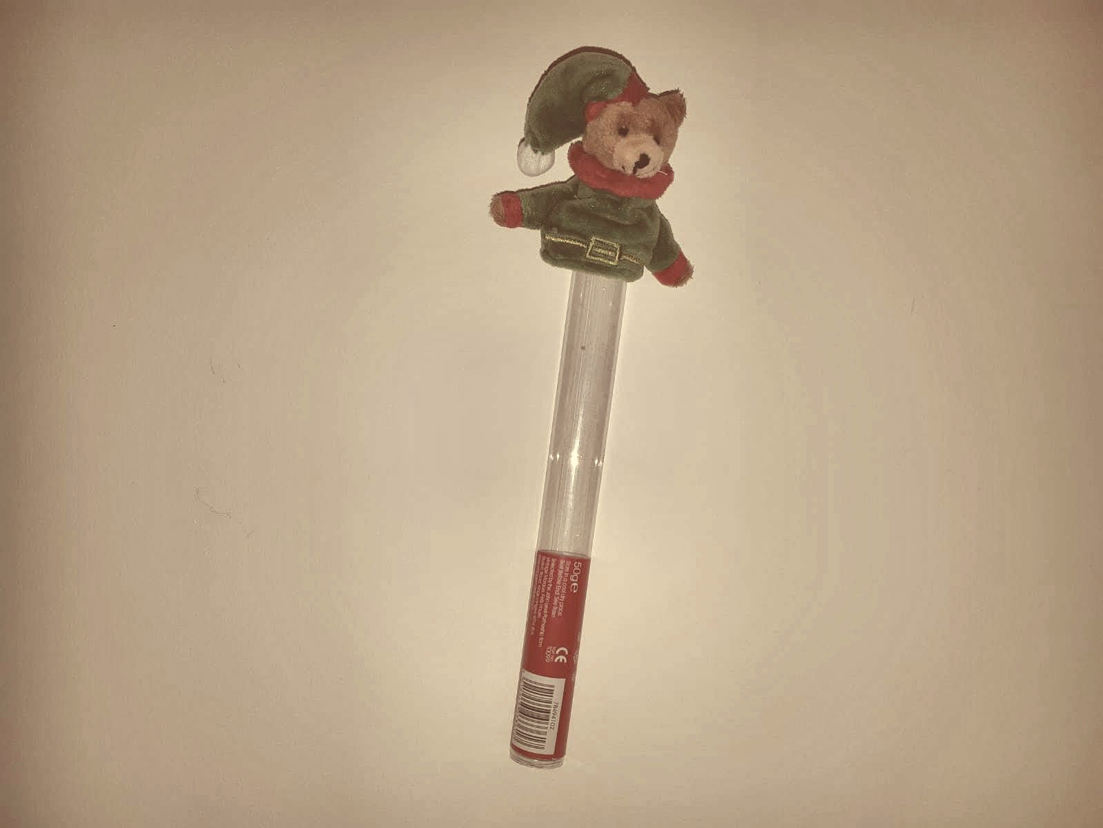 A small toy bear dressed as an elf on top of a plastic tube.