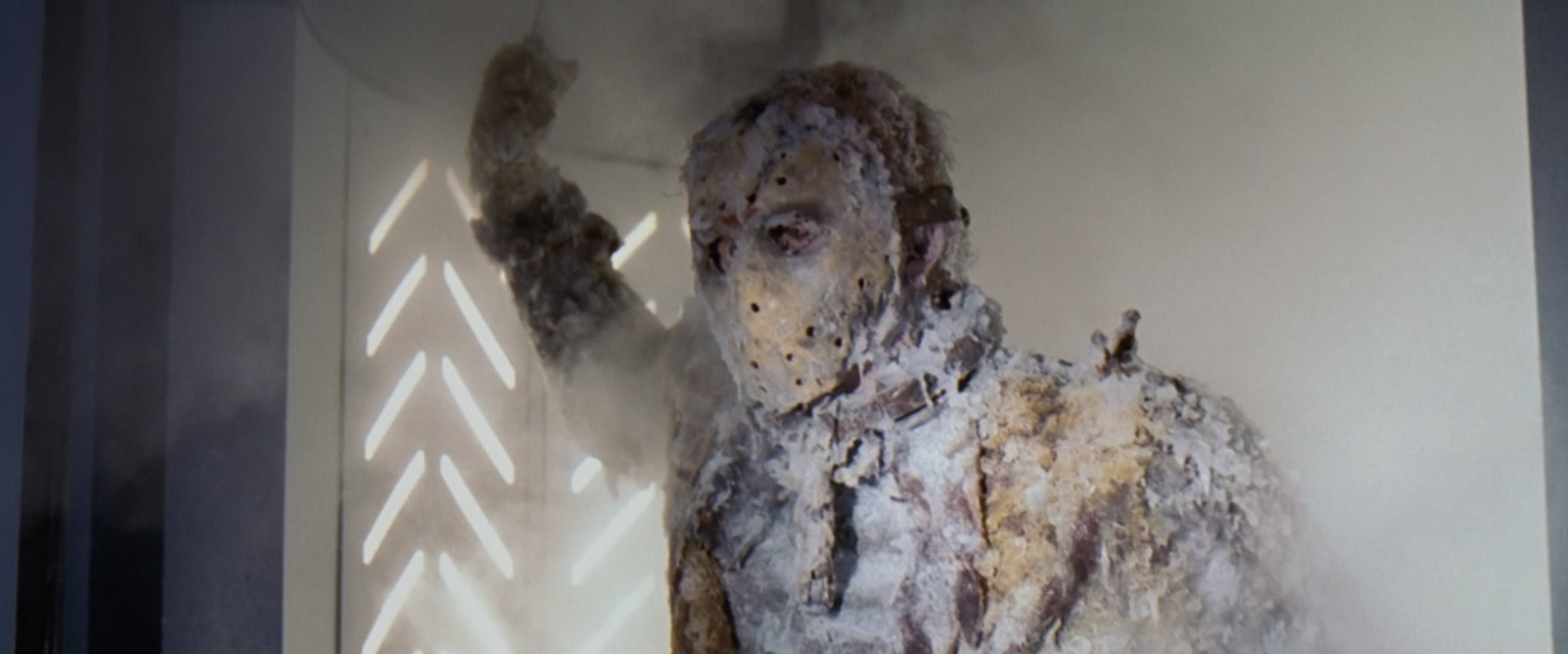 Serial killer Jason Vorhees wearing a hockey mask, being thawed from a cryogenic freezer