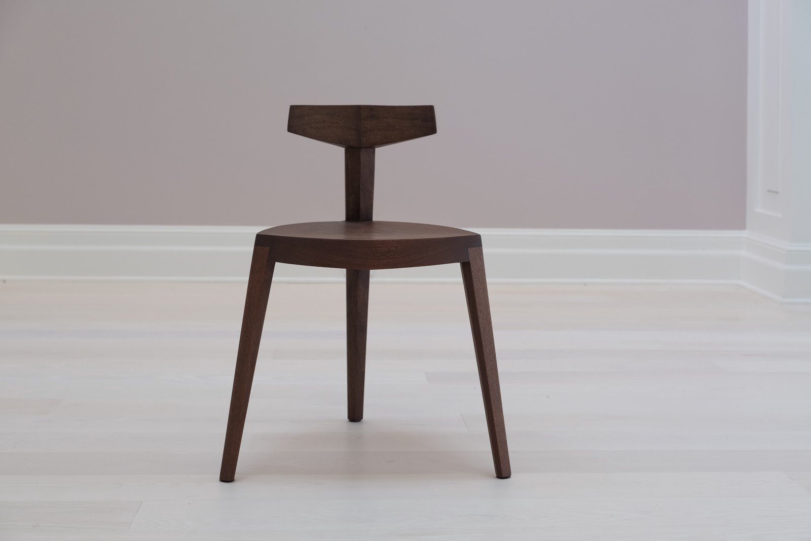 Brown wooden chair with 3 angular legs and a short back made from a vertical rectangular pole with a crossbar at the top.