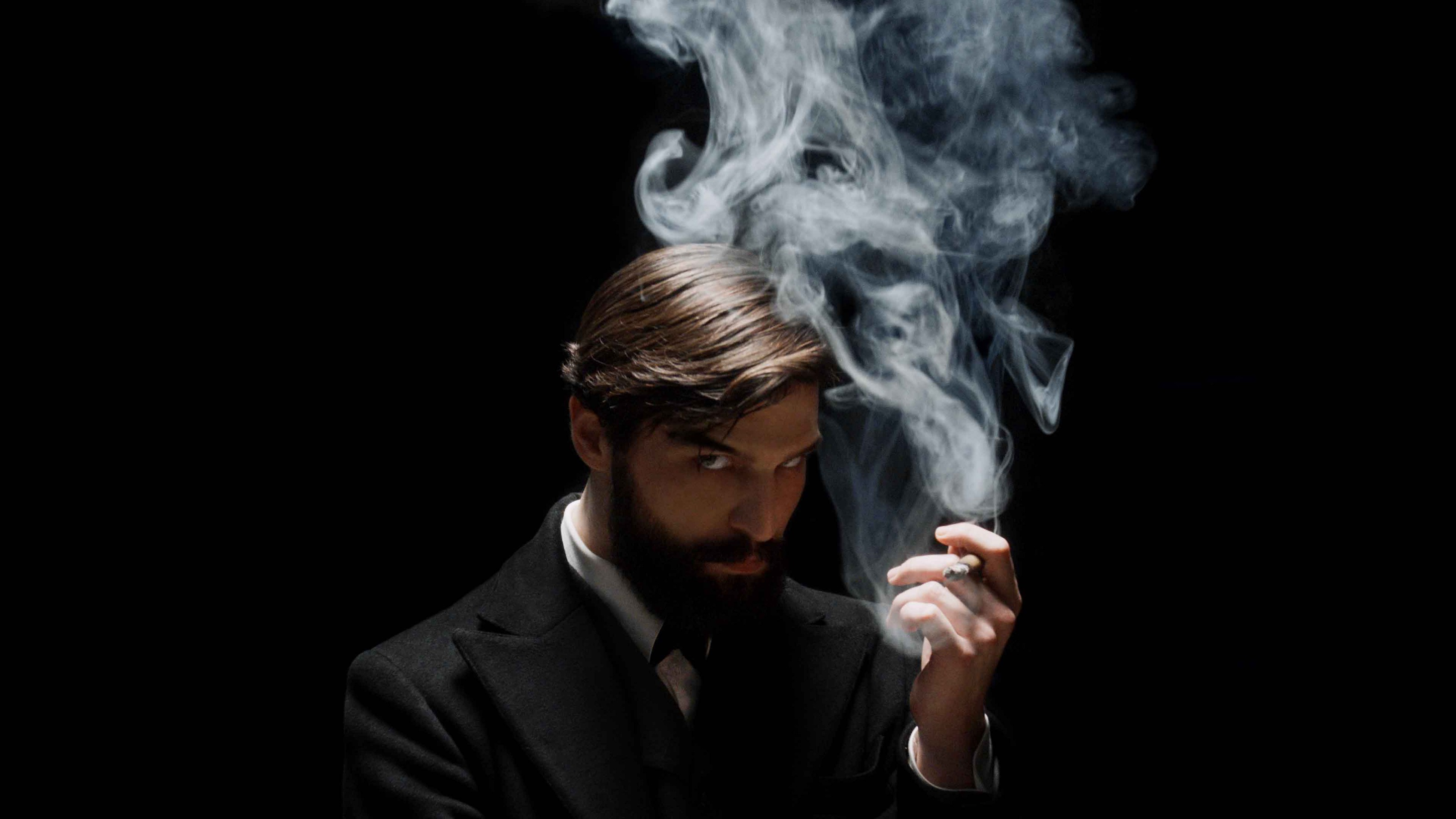 Actor Robert Finster as Sigmund Freud. He broods against a black background, with a cloud of smoke rising from his cigarette.
