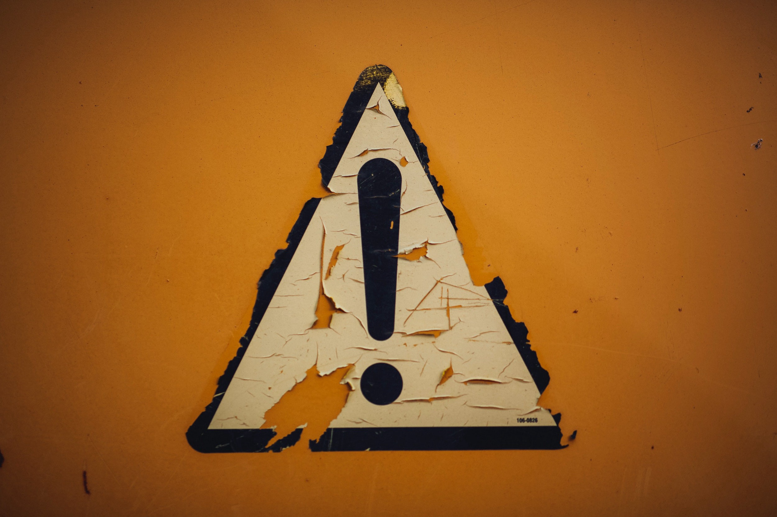 Yellow caution sign, rather beat up on a wall