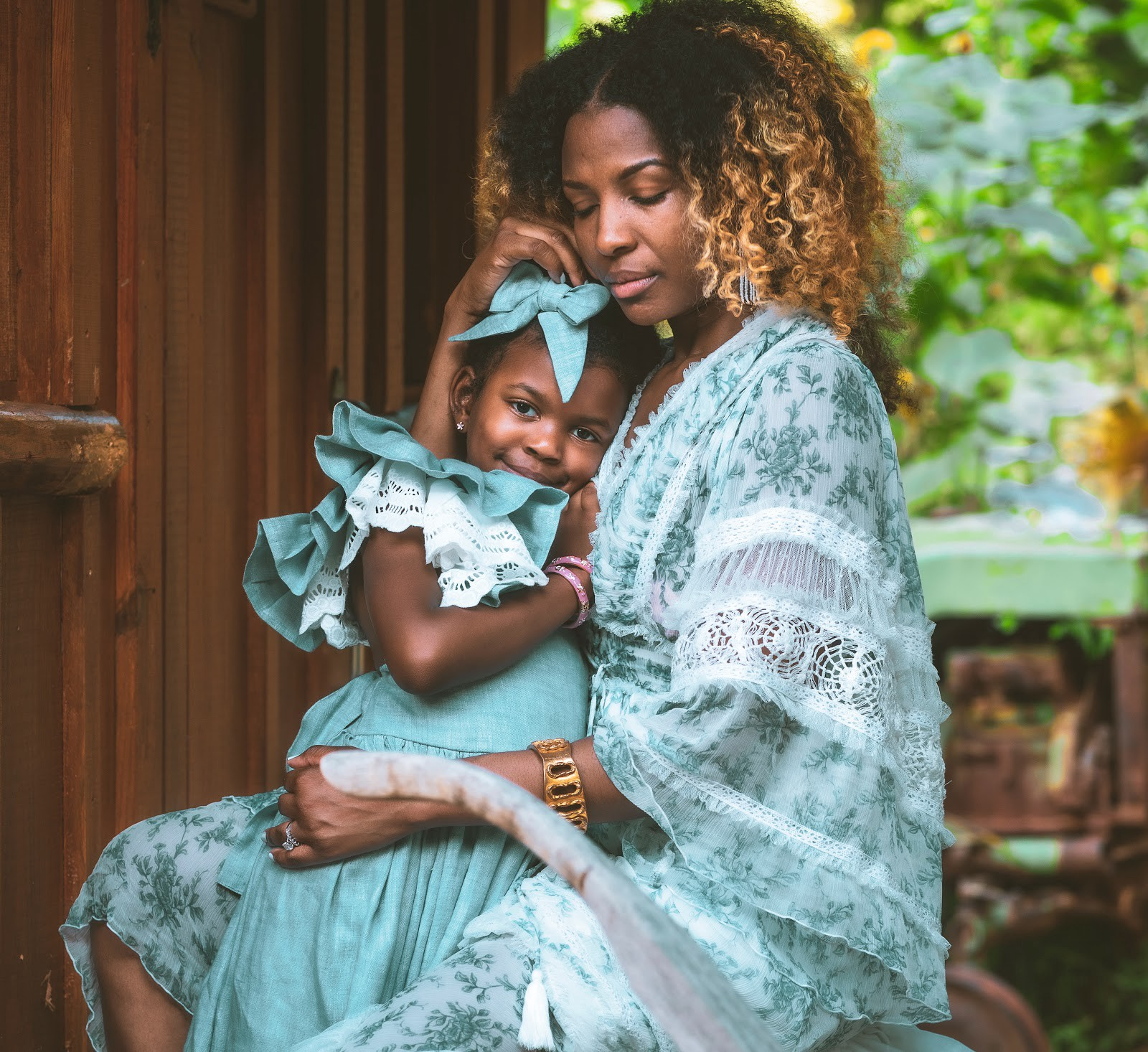 Mother with young daughter with light blue dresses in matching colors