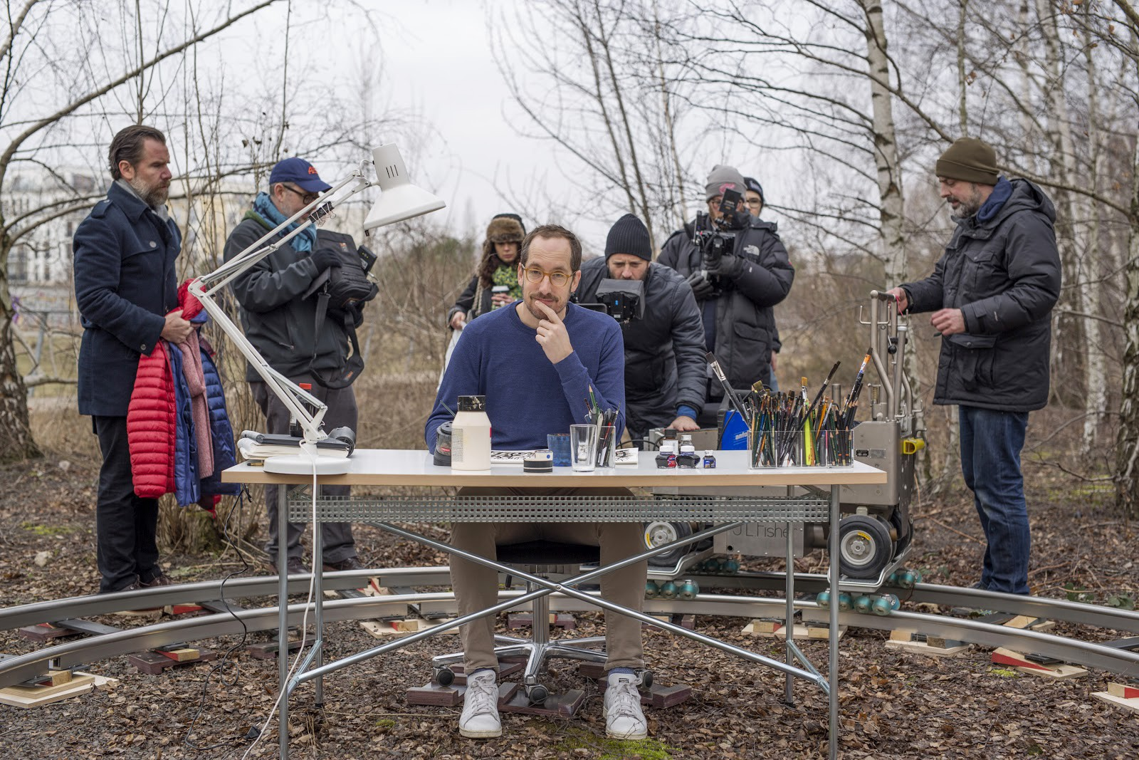 Christoph Niemann sits at a drawing desk in a Berlin park with a film crew setting up behind him.