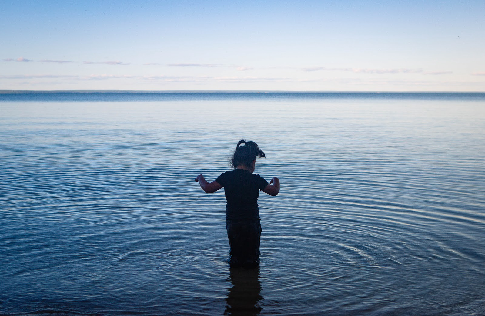 An indigenous child standing knee-deep in water which ripples around her and away toward the horizon. At Cold Lake, Alberta.