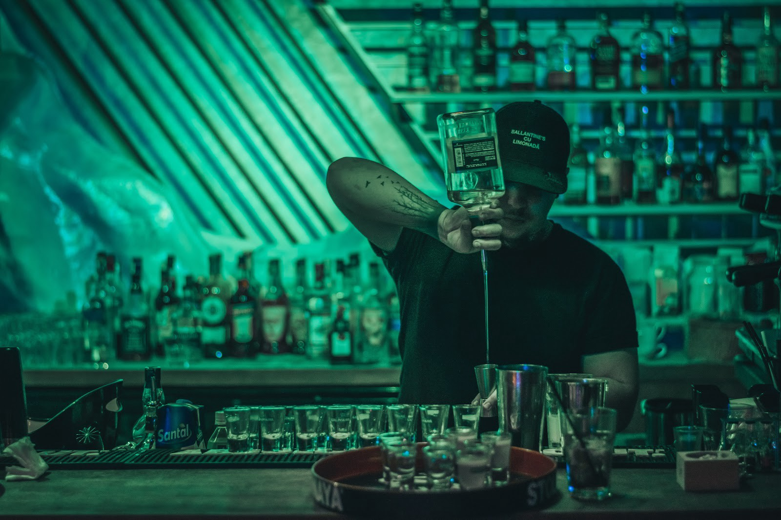 Man pouring alcohol drinks at a bar. Cannabis drinks served by budtender