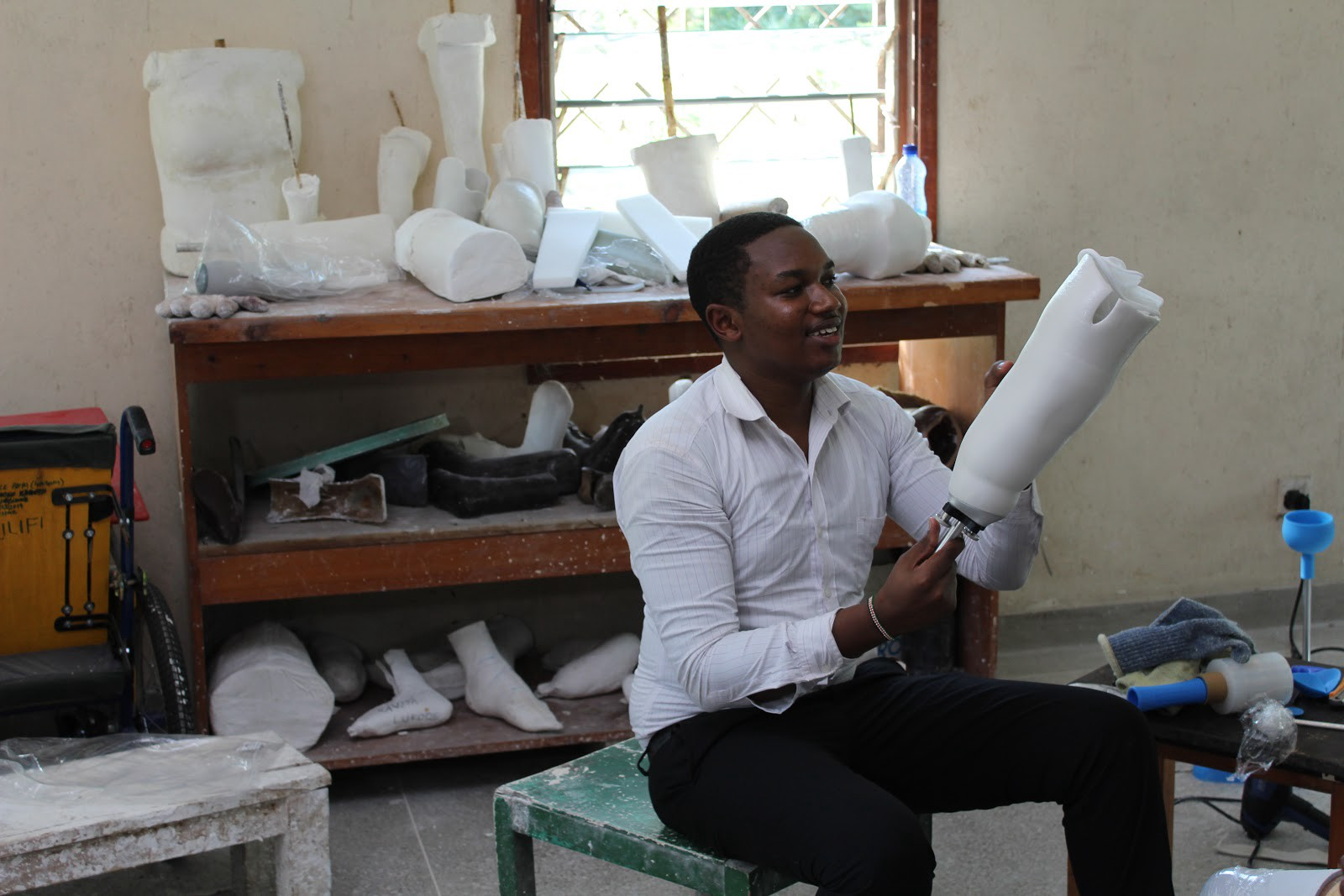 A young black entrepreneur is smiling as he holds up a white prosthetic limb to the light. Various other prototypes behind.