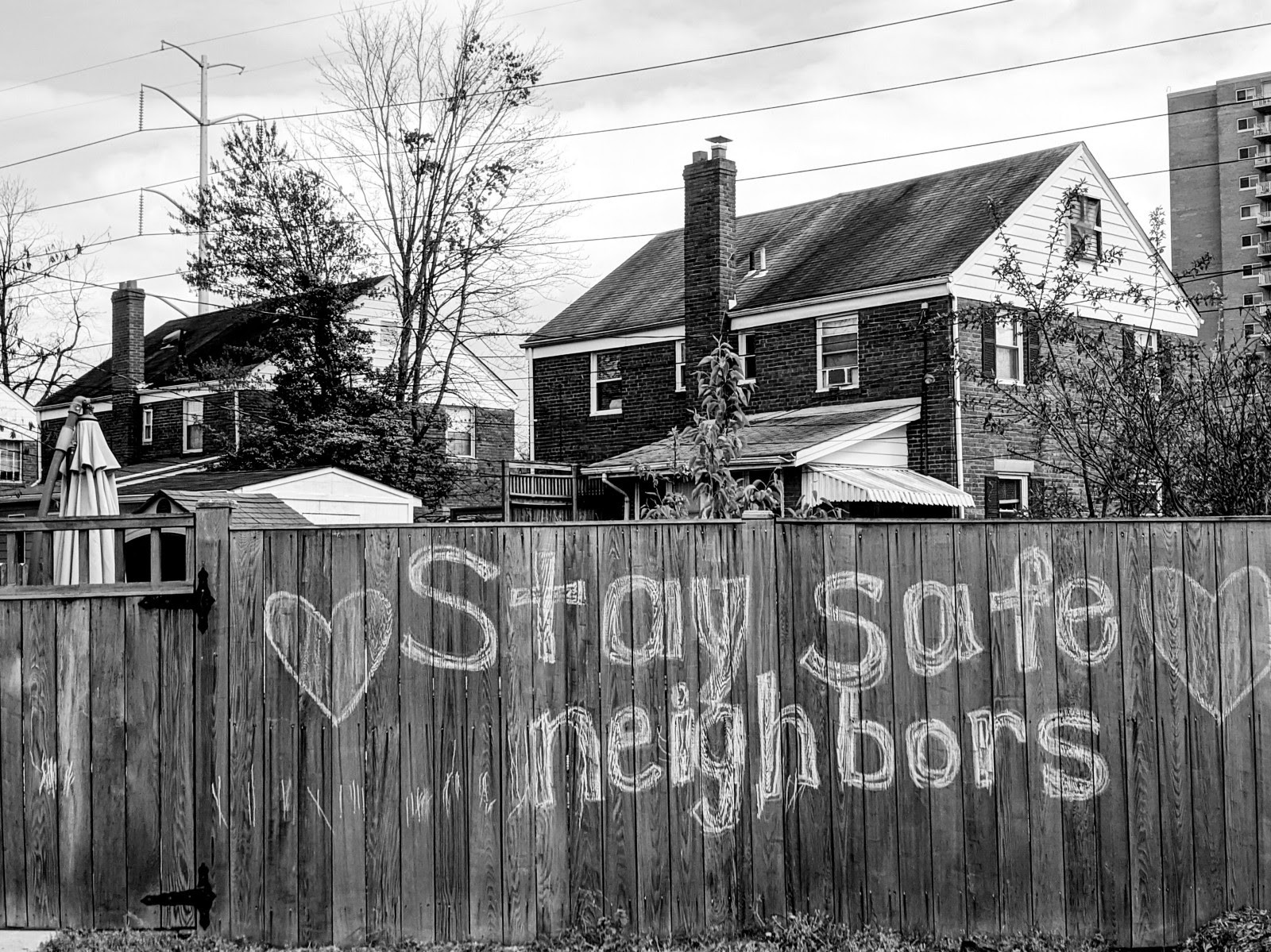 """Fence with chalk drawing that says """"stay safe neighbors"""". Houses with chimneys are seen in the background."""