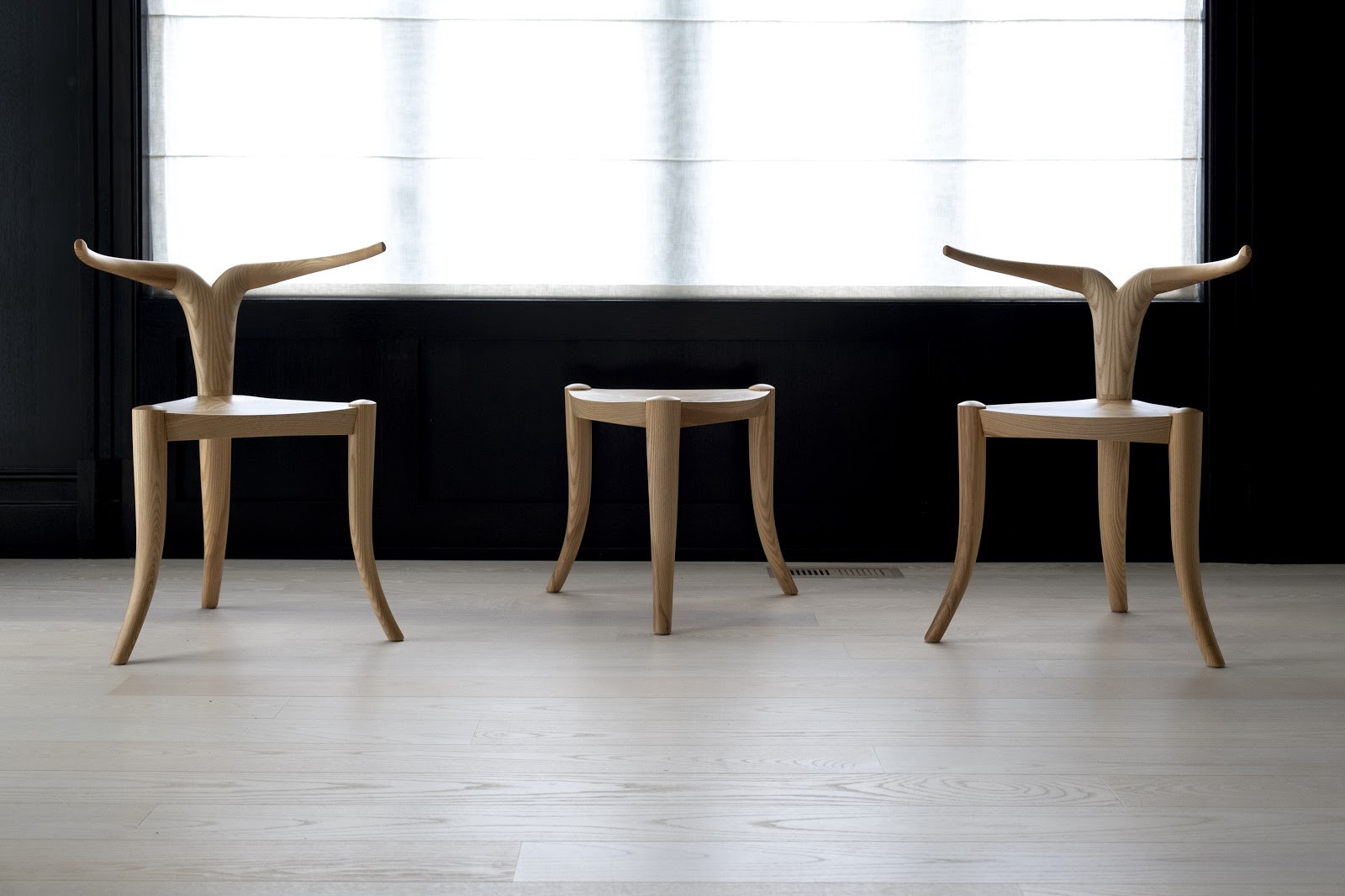 Two 3-legged chairs with antler-like backs and a 3-legged stool of the same hieght with no back. All in natural white wood.