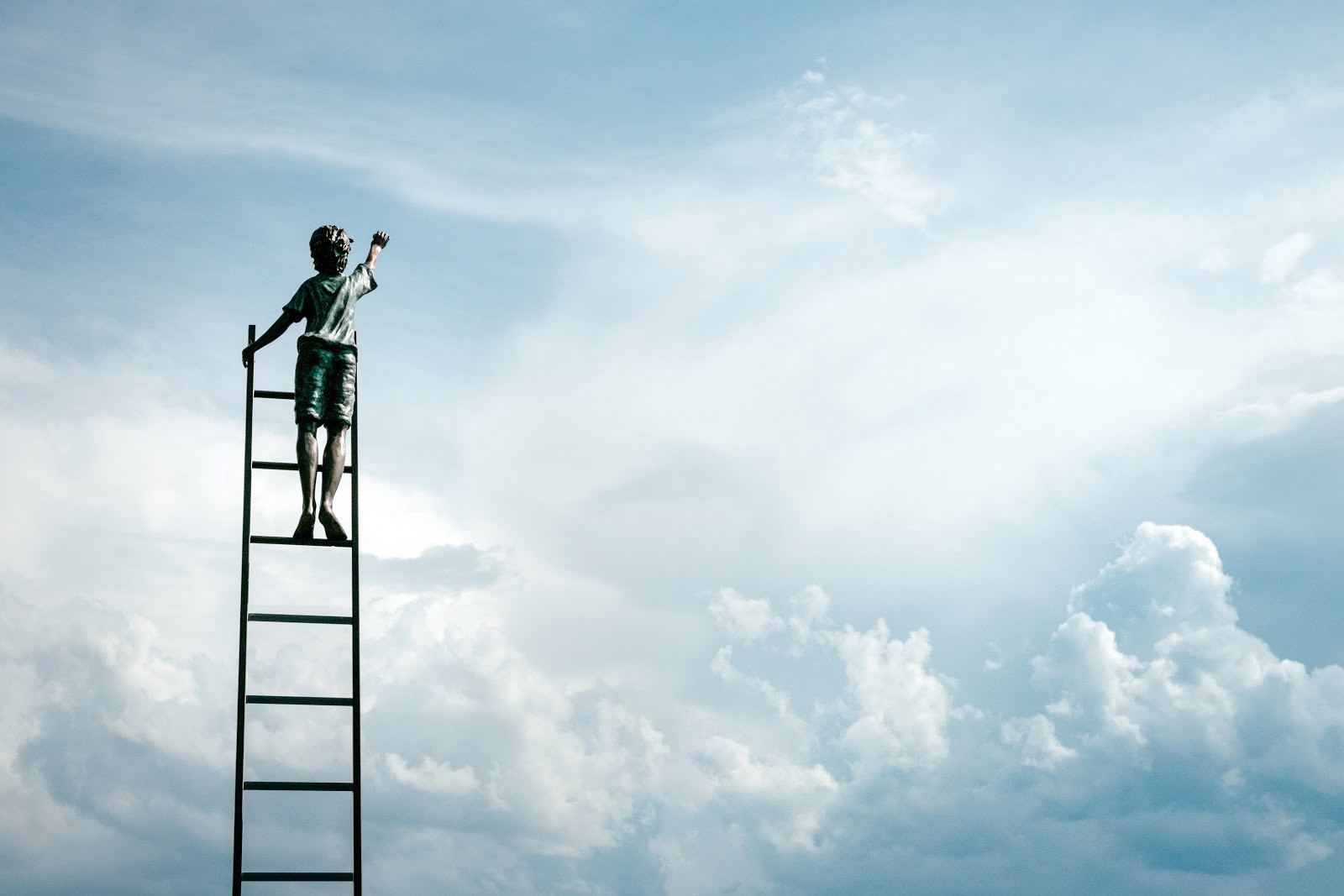 Picture of a little boy climbing a ladder into the sky and reaching for the clouds