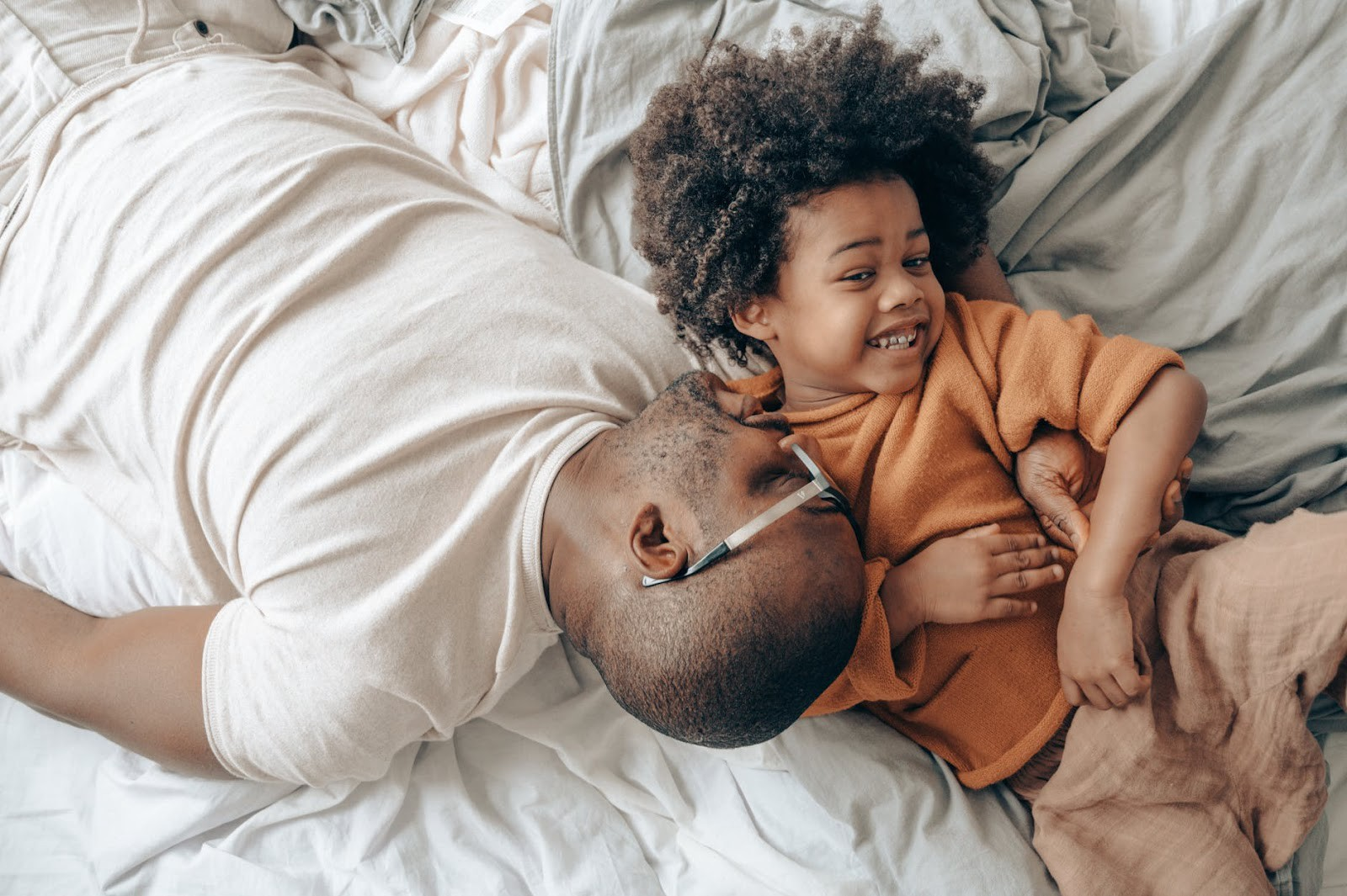 A father and his son playing on the bed
