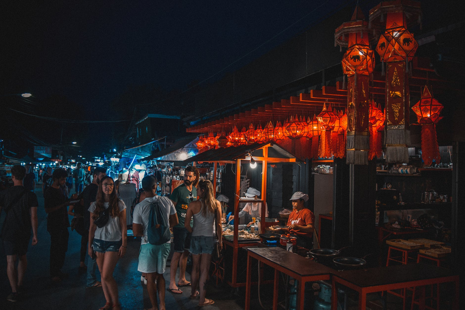 Tourists shopping at a night market in Koh Samui. There are various stalls selling food and souvenirs.