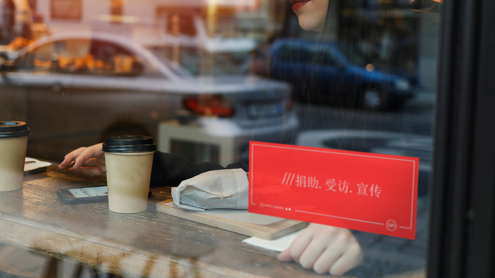 A cafe window with a red sign displaying a what3words address in Chinese
