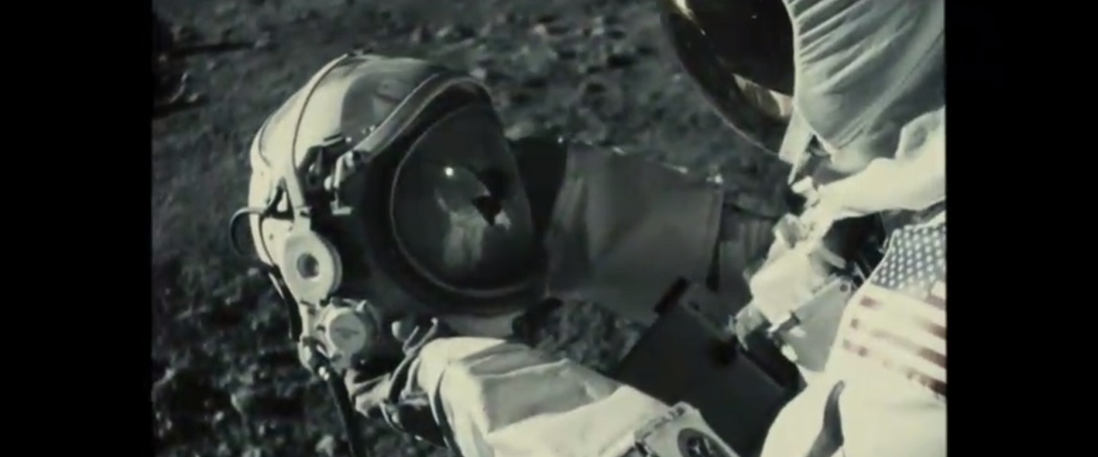 An astronaut on the moon holding a cracked helmet