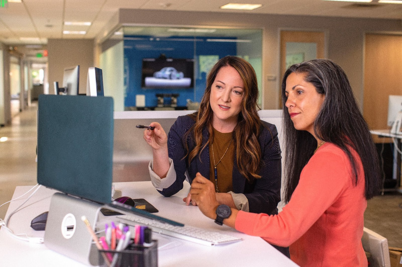 Two women discussing work in front of a computer