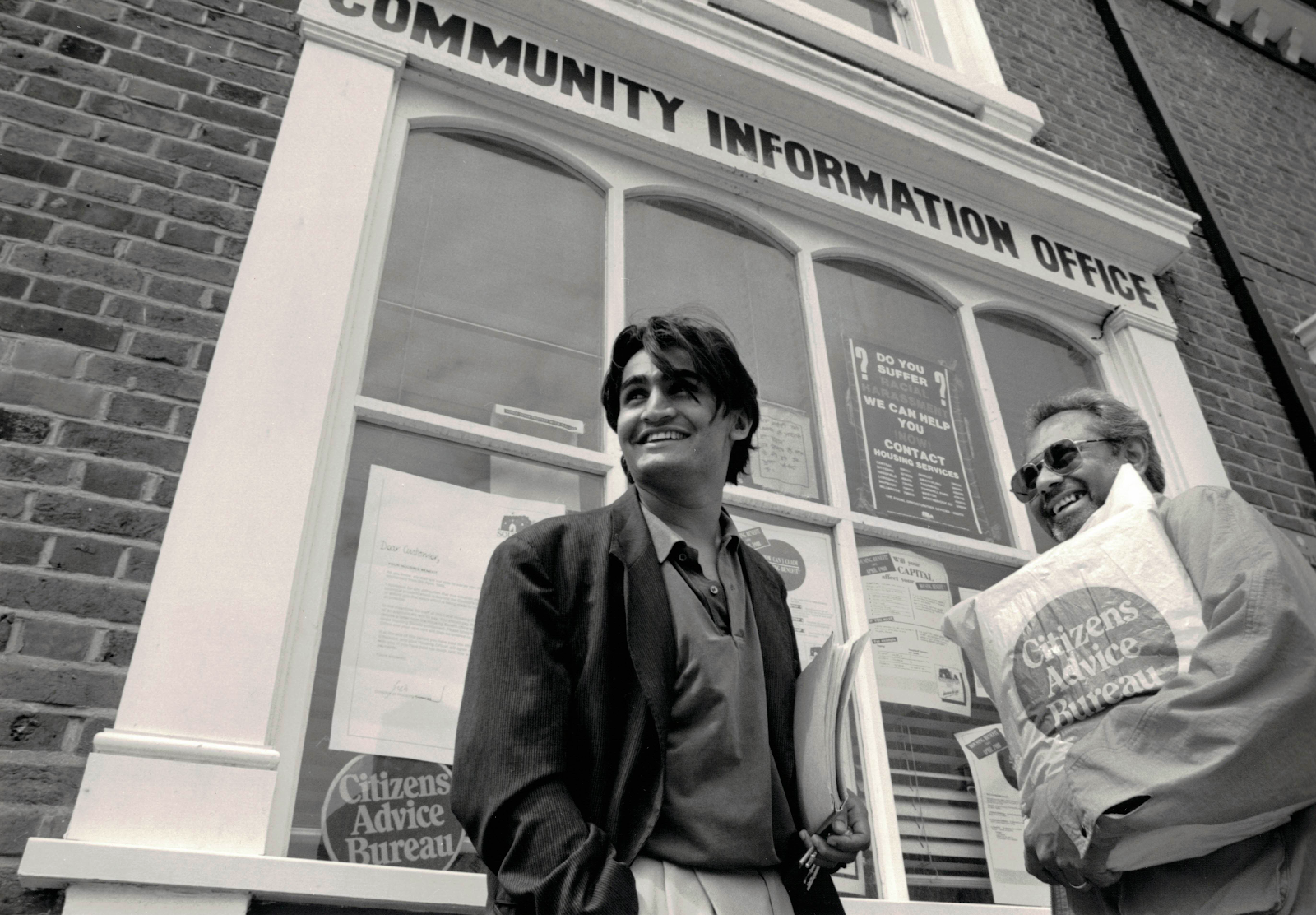 Two men standing outside a Citizens Advice office in the 1980s