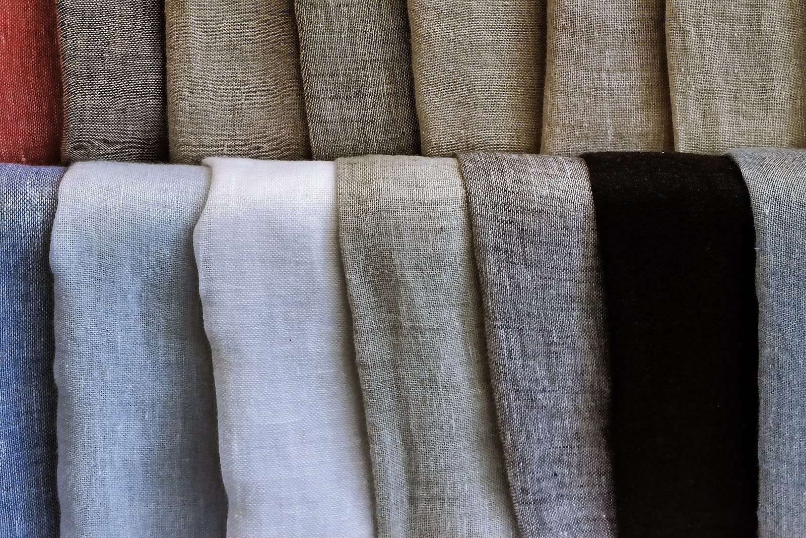 Photo of fabrics folded and hanging on top of one another. Fabrics looks like linen, in muted tones.