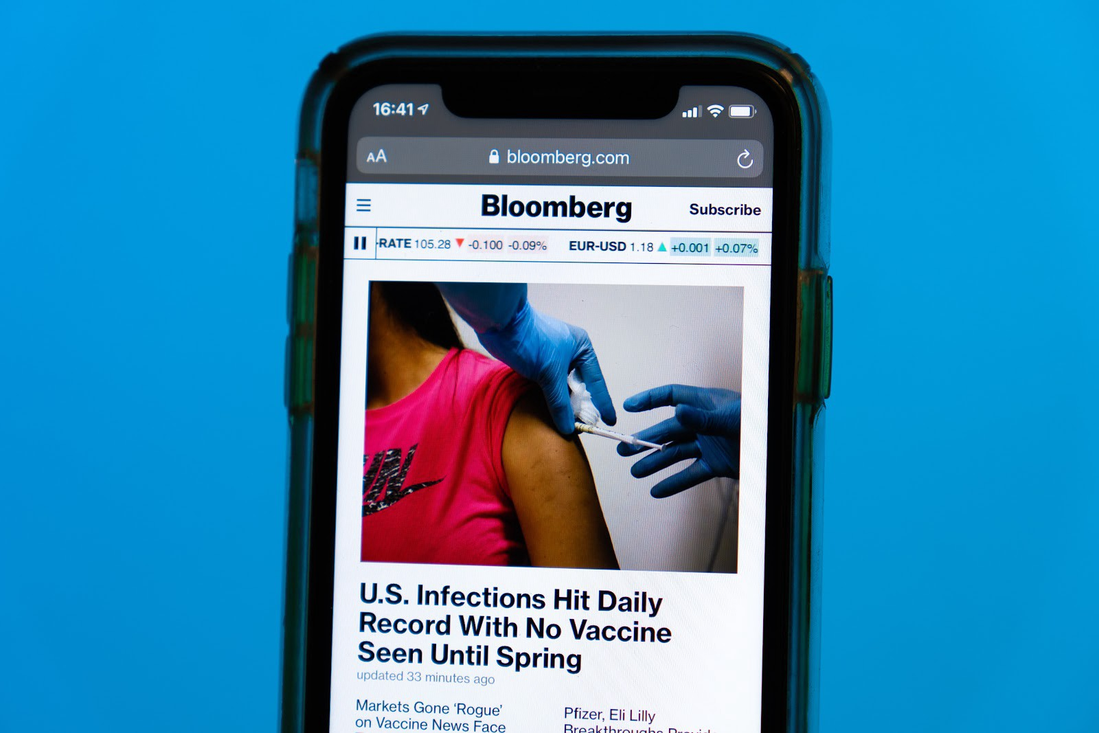 """Image of phone with article from Bloomberg titled """"U.S. Infections Hit Daily Record With No Vaccine Seen Until Spring""""."""