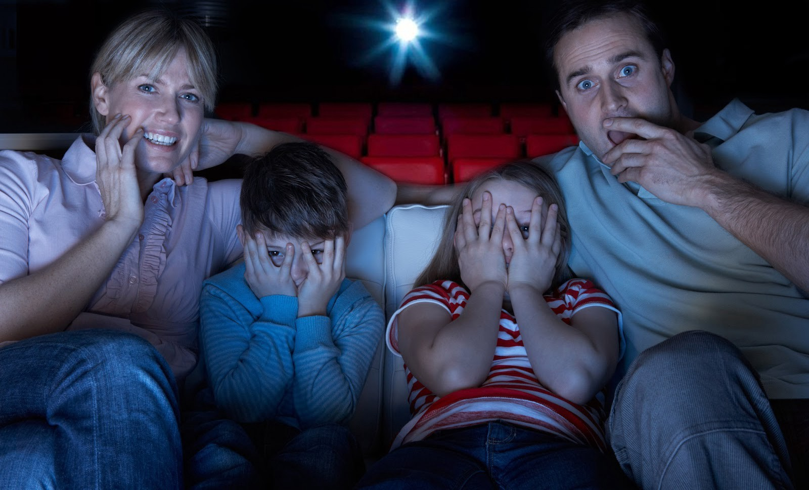 family watching a movie at a movie theater