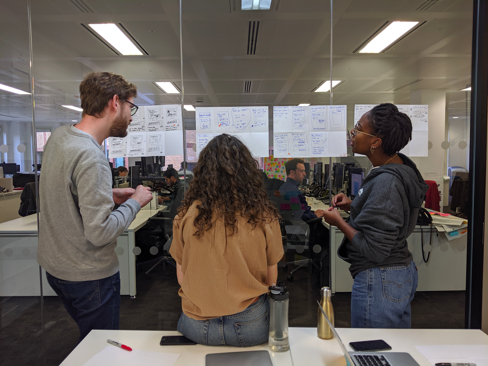 Three people in an office, looking at pages of work together