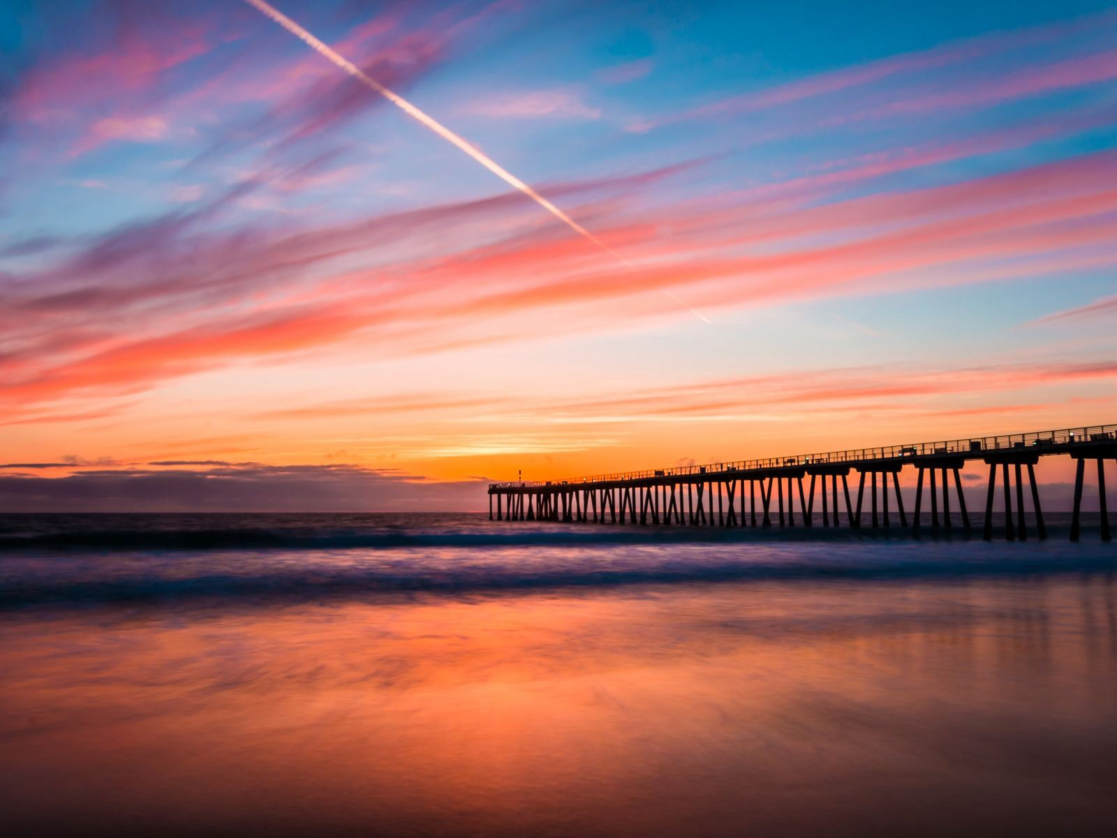 A view of Hermosa Beach during a sunset with a bridge blocking the view.