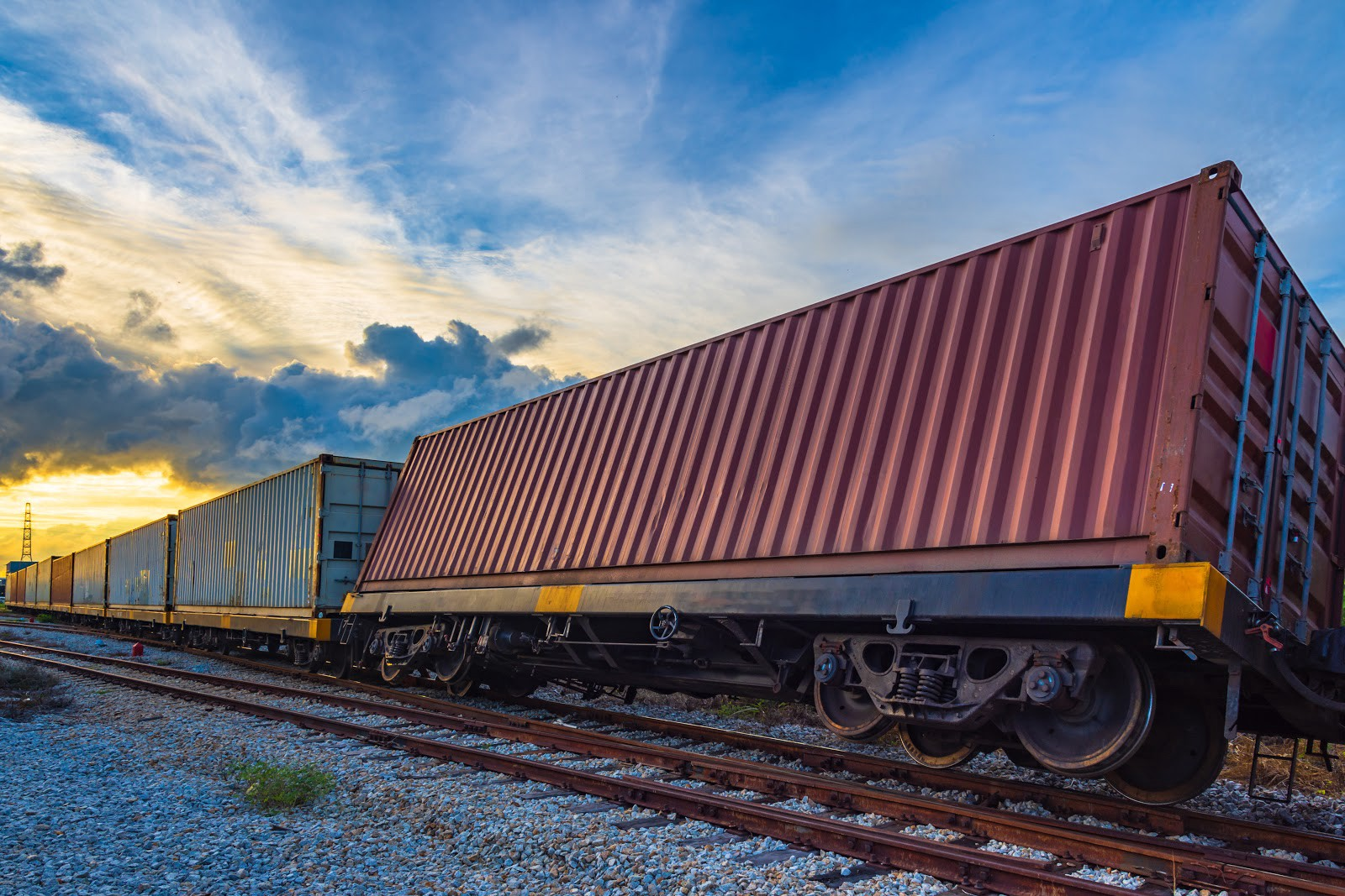 Railroad track with maroon shipping container slightly tipped over on its side
