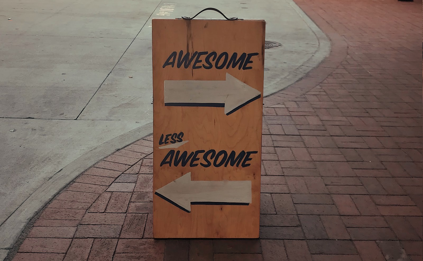 """Sign with an arrow pointing to the right that indicates """"Awesome,"""" and an arrow pointing to the left that says """"Less Awesome"""""""