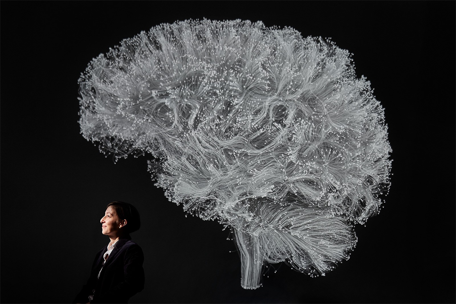 Professor Danielle Bassett poses under a black-and-white illustration of the brains complex structural network.
