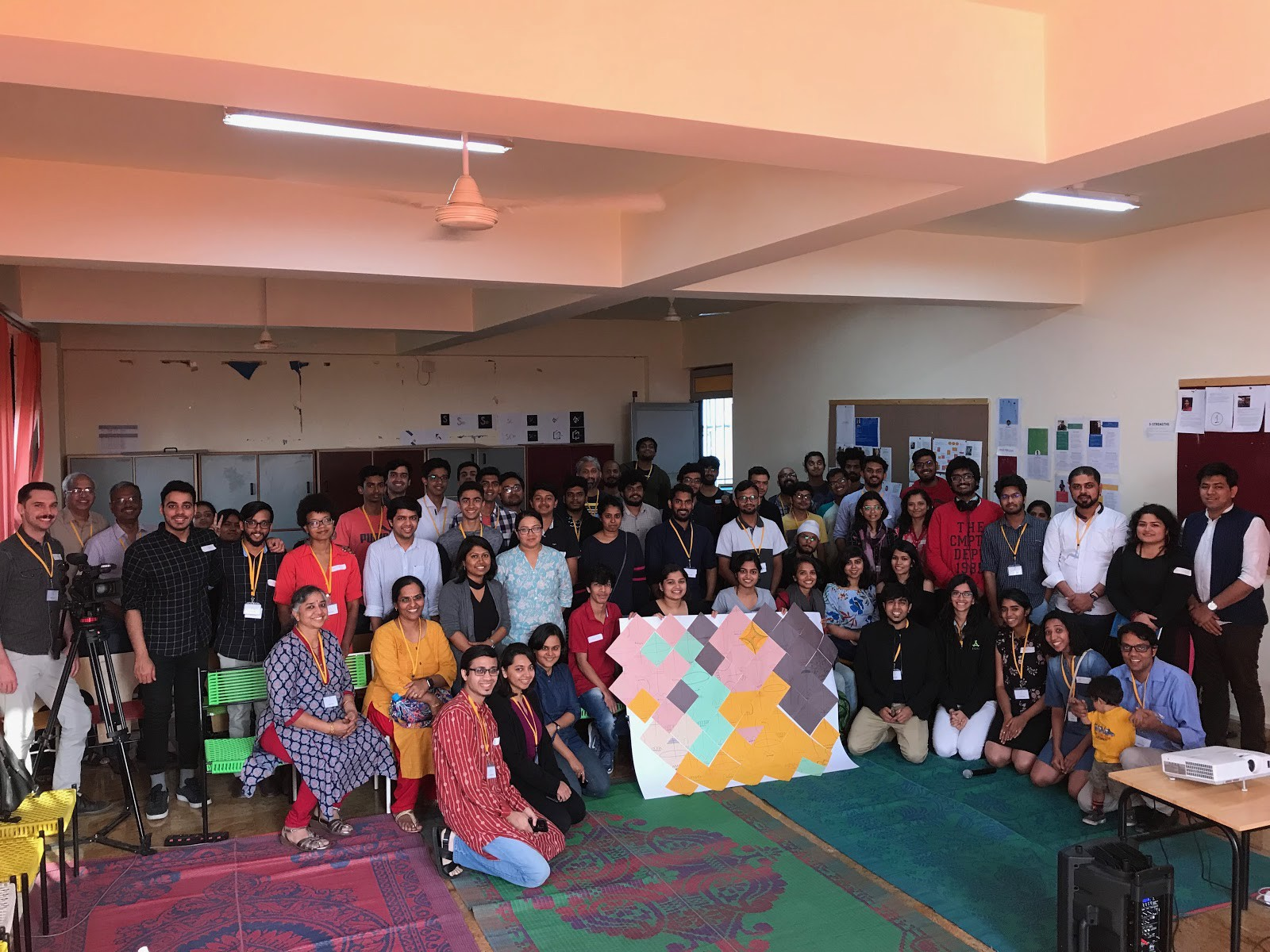 """A group picture of the participants of PCD Bangalore—group of people in the center are holding the """"Data Selfie"""" installati"""