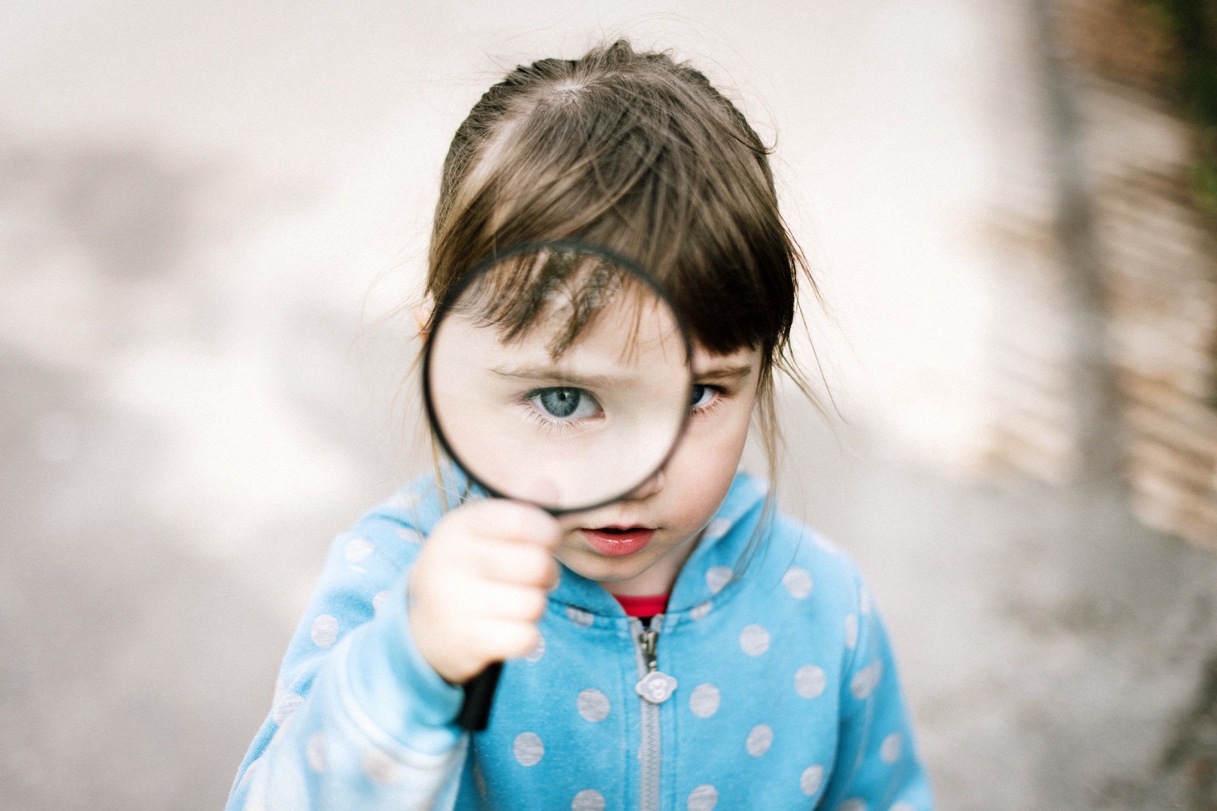 Young girl with magnifying glass making her eye look very large.