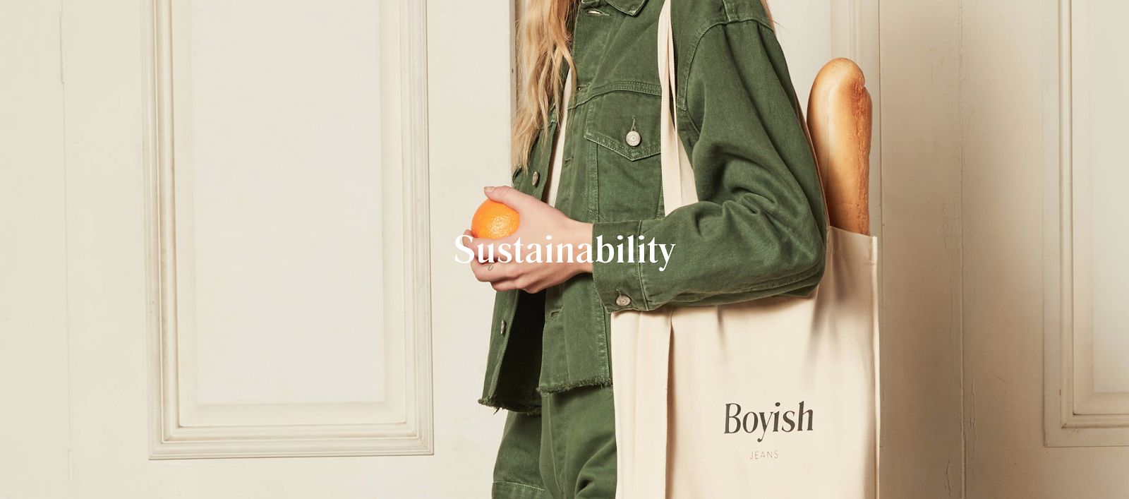 """Photo of a woman in a green jacket holding an orange and a Boyish branded bag. Word """"Sustainability"""" on top of photo."""