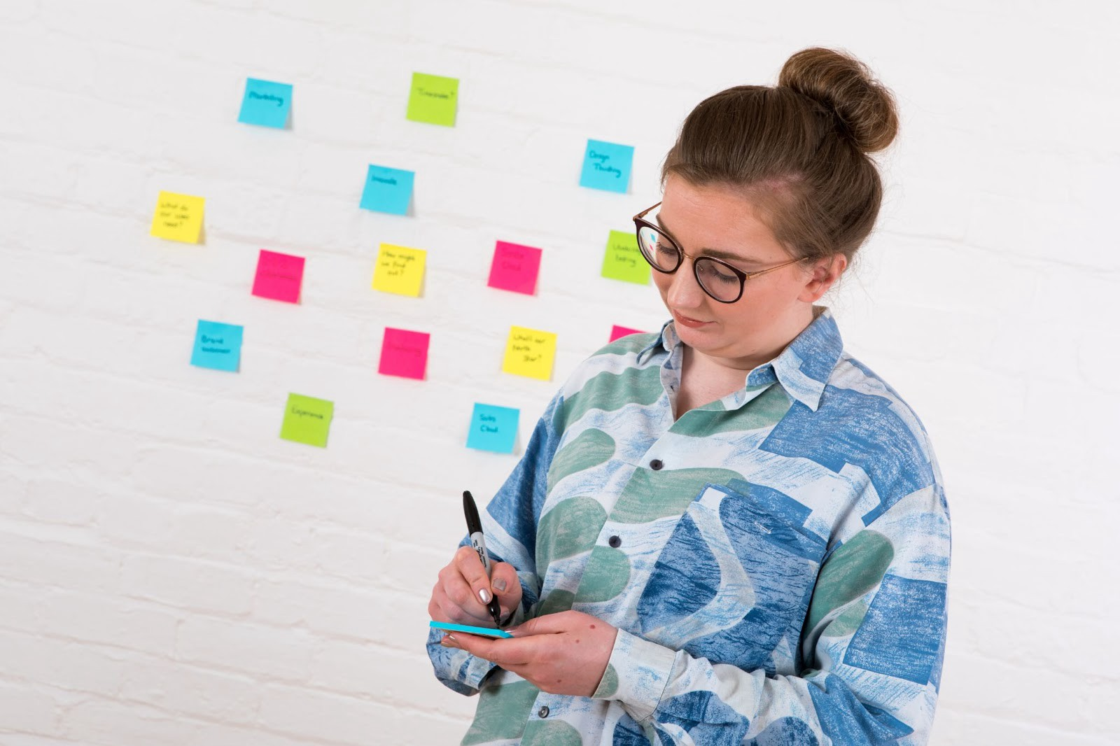 Angela standing in front of a white wall with colorful sticky notes on it. She is writing with a sharpie on a blue note.