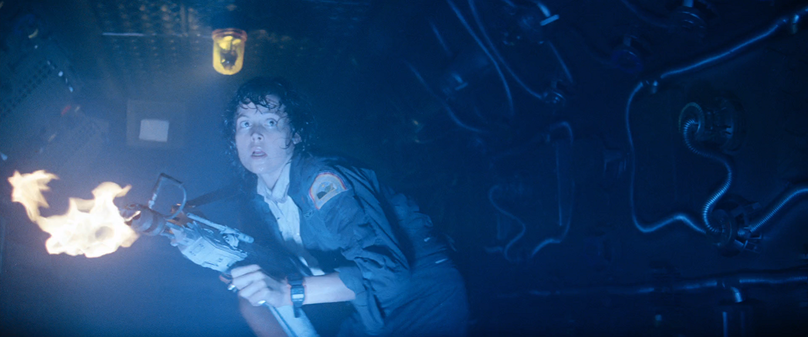Ellen Ripley holding a flamethrower and walking cautiously down a corridor of a spaceship