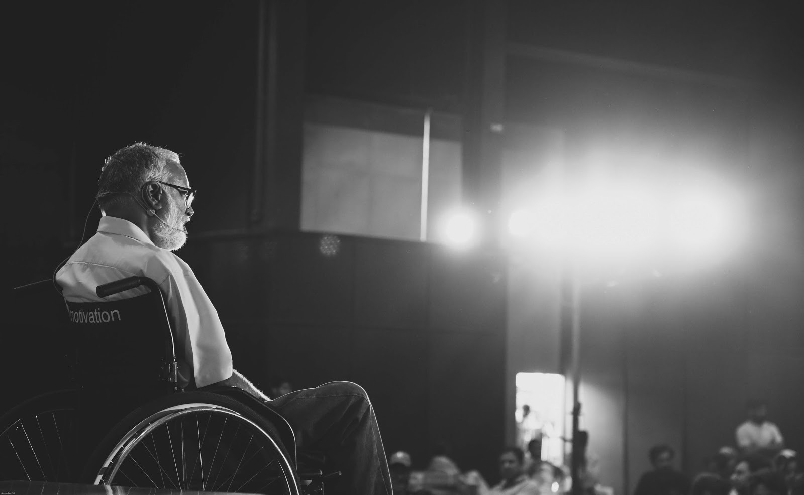 Black and white photo of Mohan Sundaram—Founding CEO & Director of Artilabs. He is in a wheelchair facing an audience.