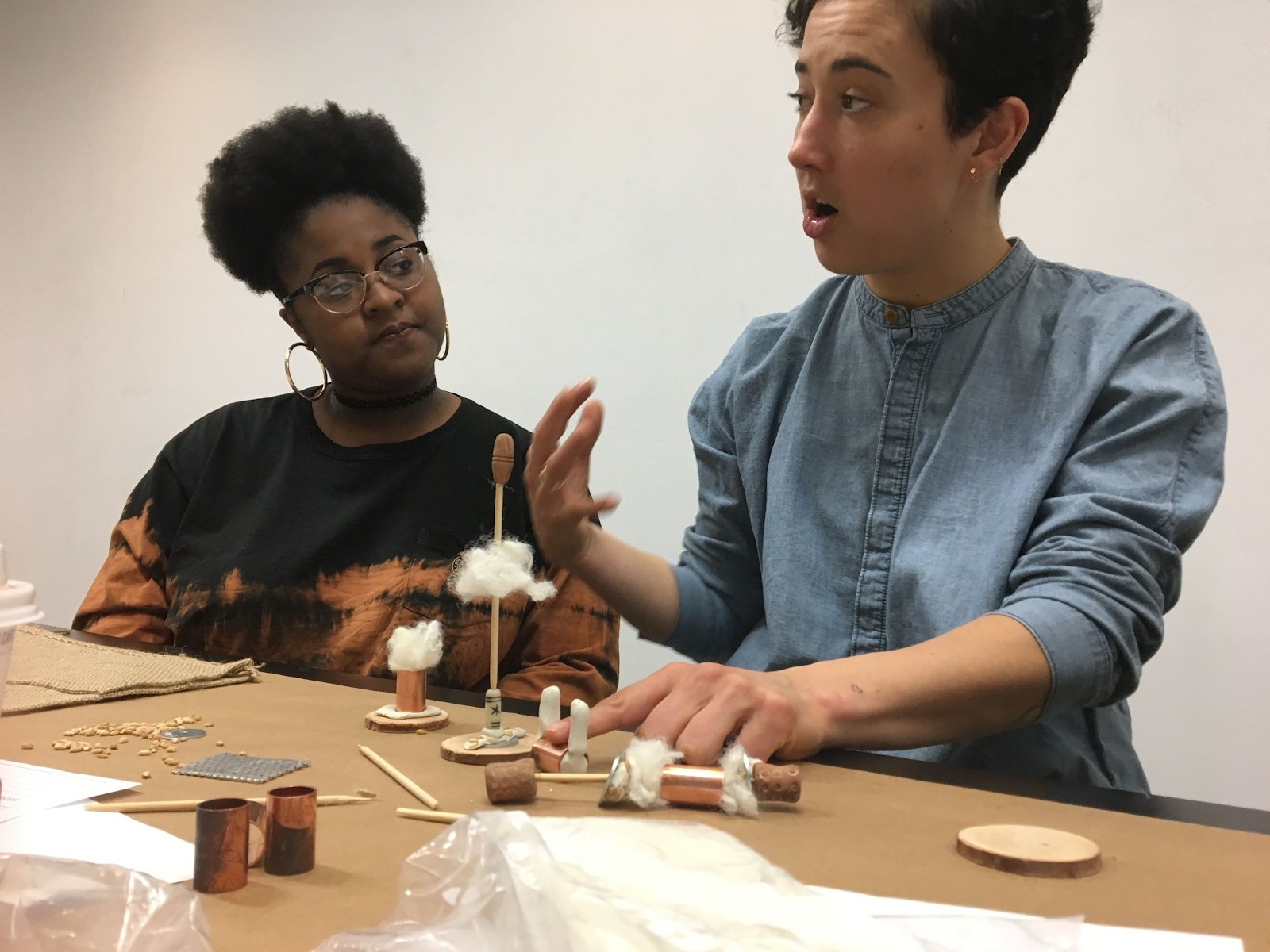 Image from workshop: two students at a table presentng crafts from a future world.
