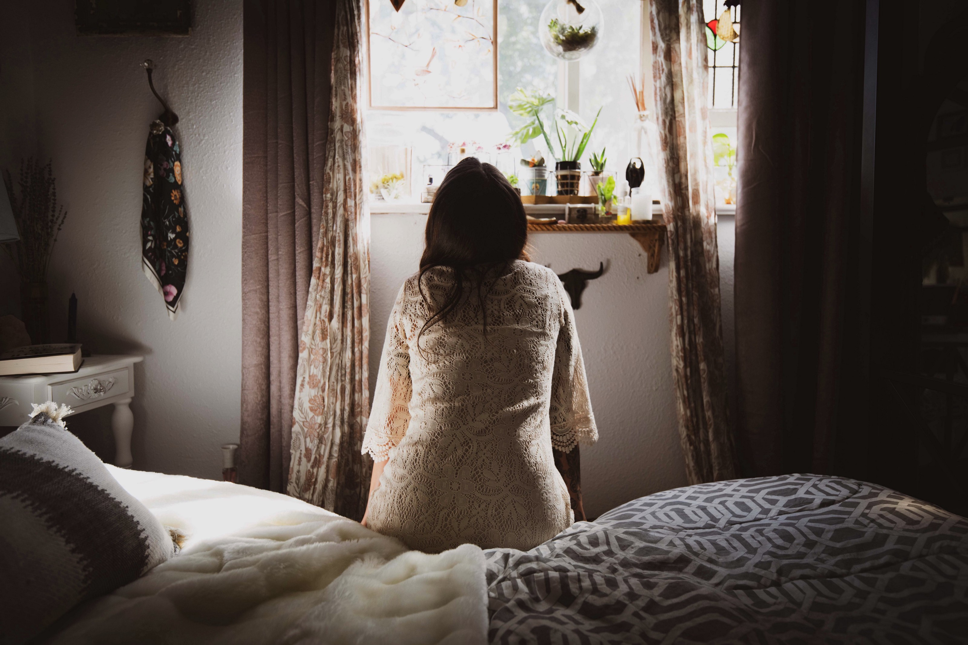 Woman sitting at edge of bed looking towards window trying to decide how to move forward. Her back profile is seen