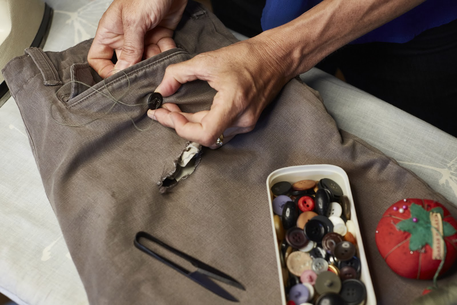 Closeup of someone using needle and thread to replace a button on the back pocket of a pair of pants.