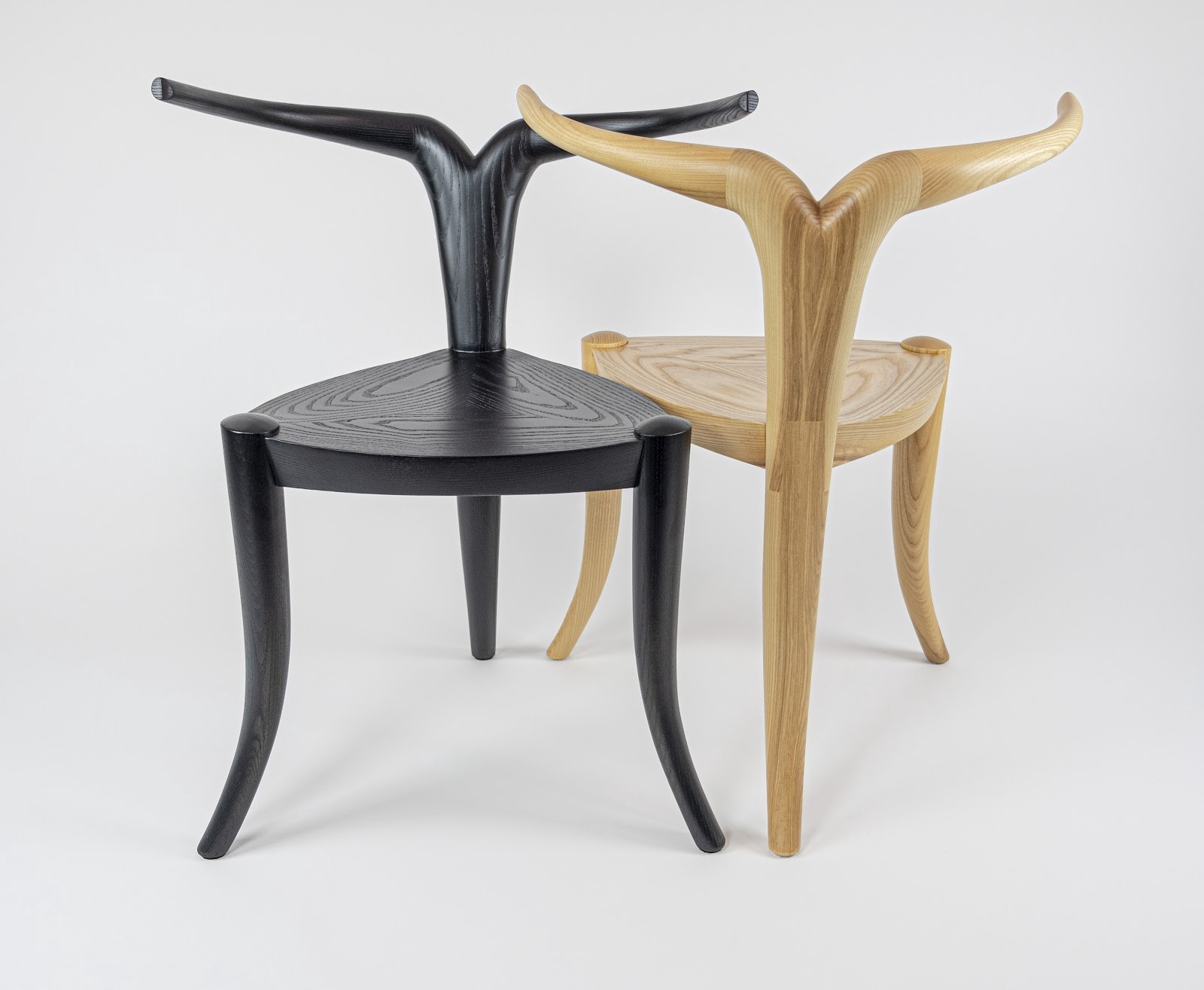 Two 3-legged wood chairs, one natural, one black. For a back, each has a single pole that splits into two antler-like arms.