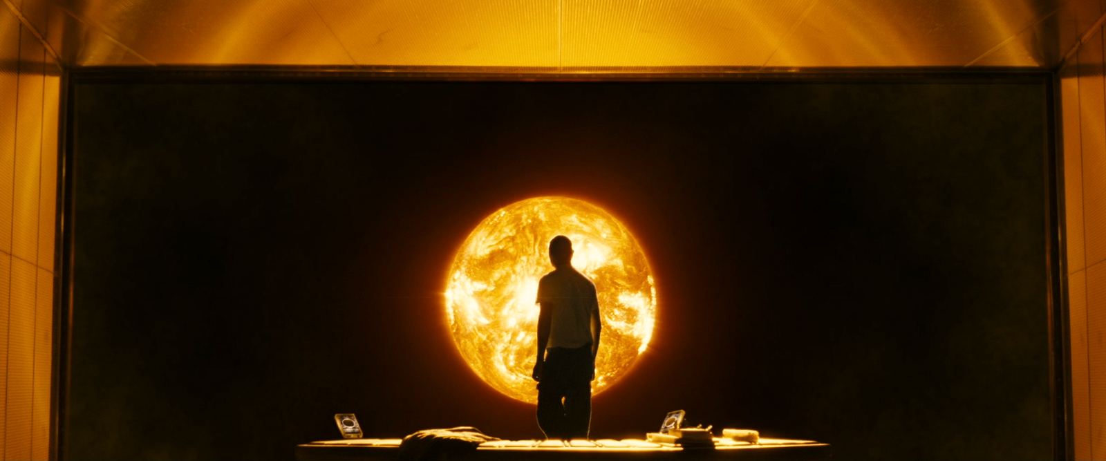 A man silhouetted in front of a screen displaying the sun