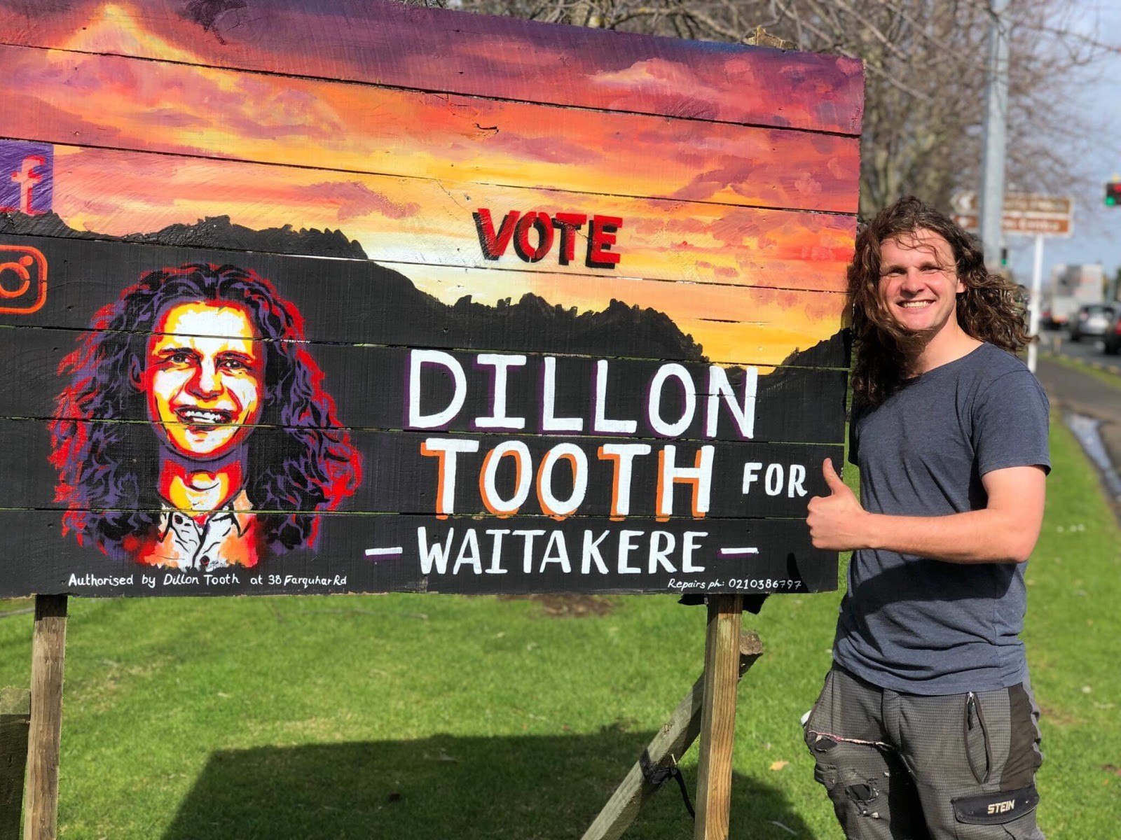 Dillon standing next to one of his hand painted signs with thumbs up