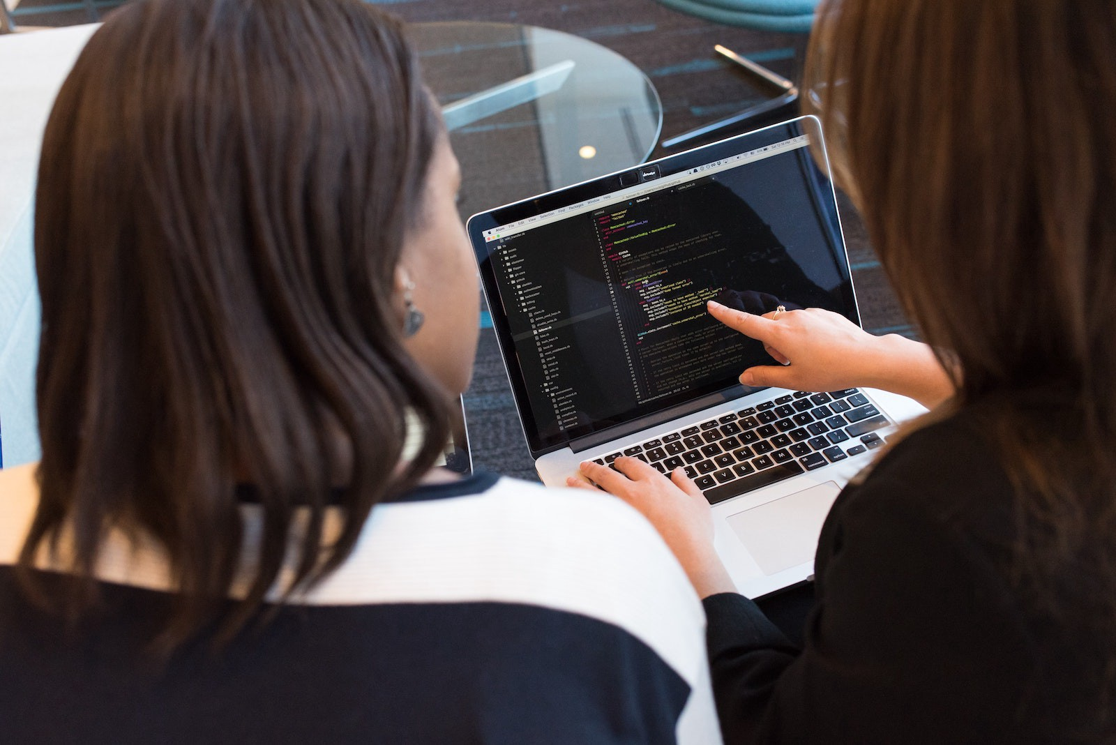 Two women look at a computer screen; one points at code displayed on the screen