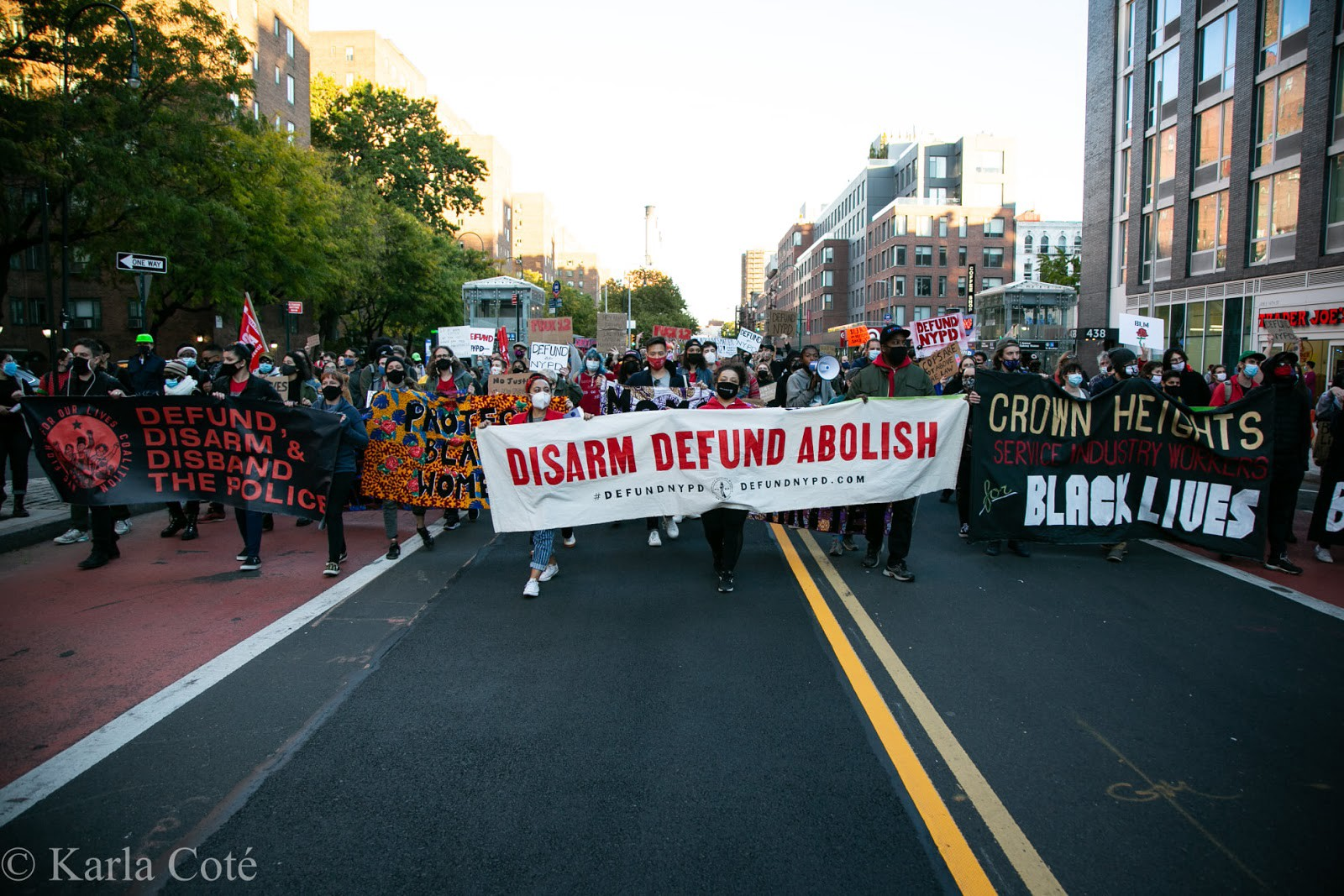 """Image depicts hundreds of protesters gathered on October 17, 2020 to support the demand to defund the NYPD, tax the rich, and stop mass layoffs. The most prominent banners held by protesters in this image read """"Defund, Disarm & Disband the Police,"""" """"Protect Black Women,"""" """"Disarm Defund Abolish 